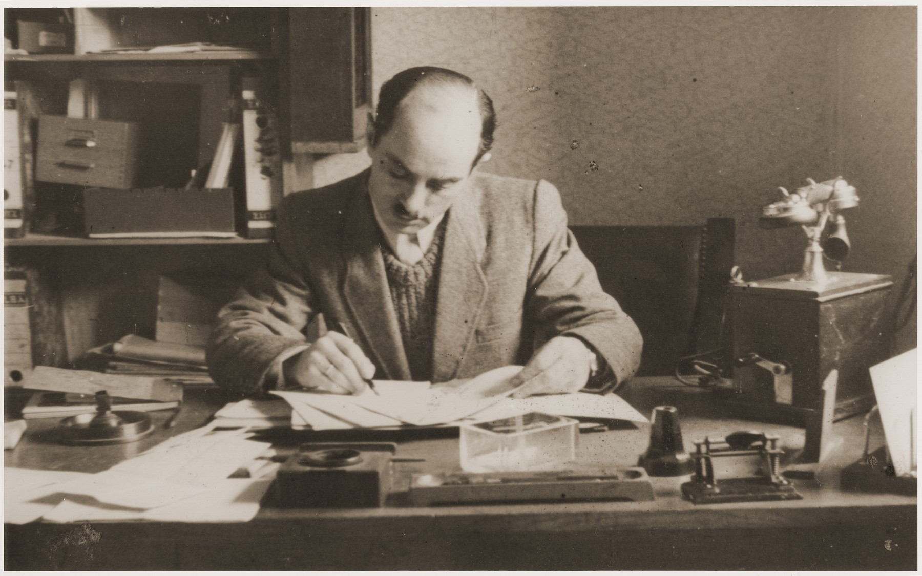 Camp administrator Noach Miedzinski works at his desk in the Kibbutz Nili hachshara (Zionist collective) in Pleikershof, Germany.  Some of the objects on his desk once belonged to Nazi war criminal Julius Streicher.