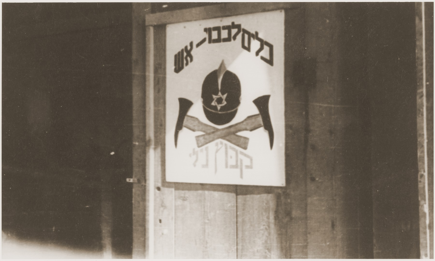 A Hebrew sign posted on the door of a shed indicates that firefighting equipment for the Kibbutz Nili hachshara (Zionist collective) is stored here.