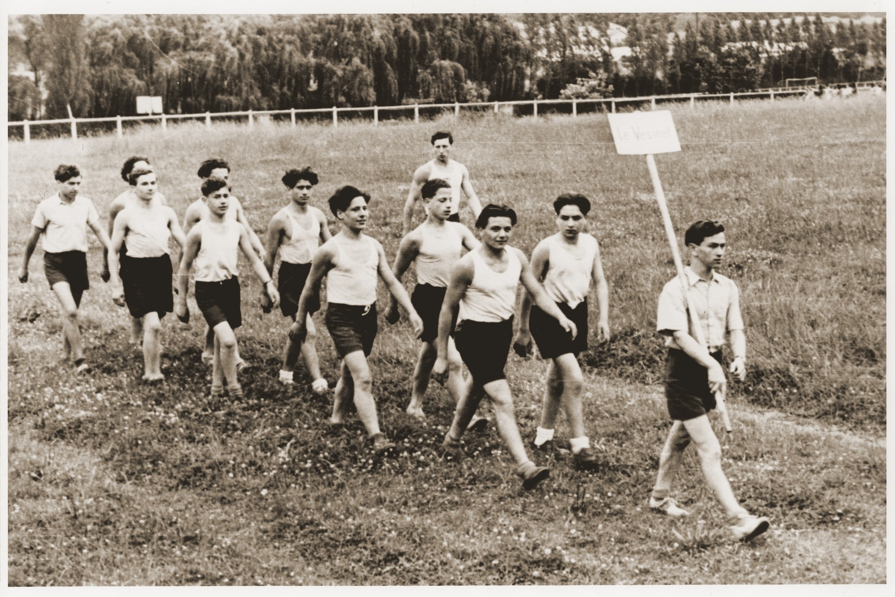 Jewish youth from the Le Vésinet children's home march down a grassy track during a sports meet.  Pictured from left to right are Theodo (Bubi) Lowy, Jozef Szwarcberg, Romek Wajsman, Leon Friedman, Hershel Unger, Edgar ?, Jakob Kapelusz and Beniek Mrowka.