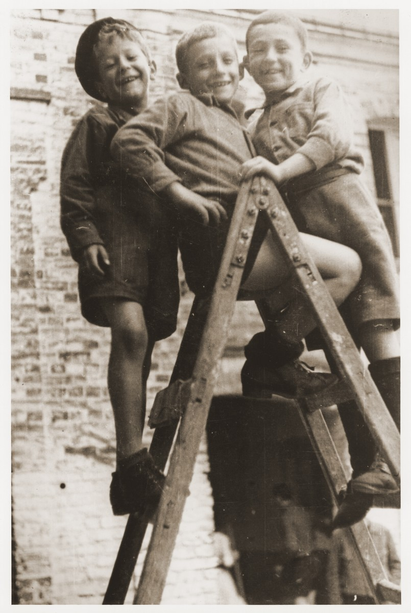 Three young boys who were members of the Buchenwald children's transport, pose on a ladder at the OSE (Oeuvre de Secours aux Enfants) children's home in Ecouis.    Pictured from right to left are David Perelmutter, Izio Rosenman from Demblin Poland and Yisrael Meir (Lulek) Lau.
