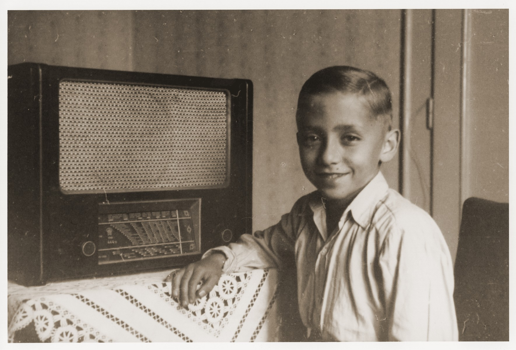 Rene Guttmann poses beside a large radio in the Mann family home in Kosice.