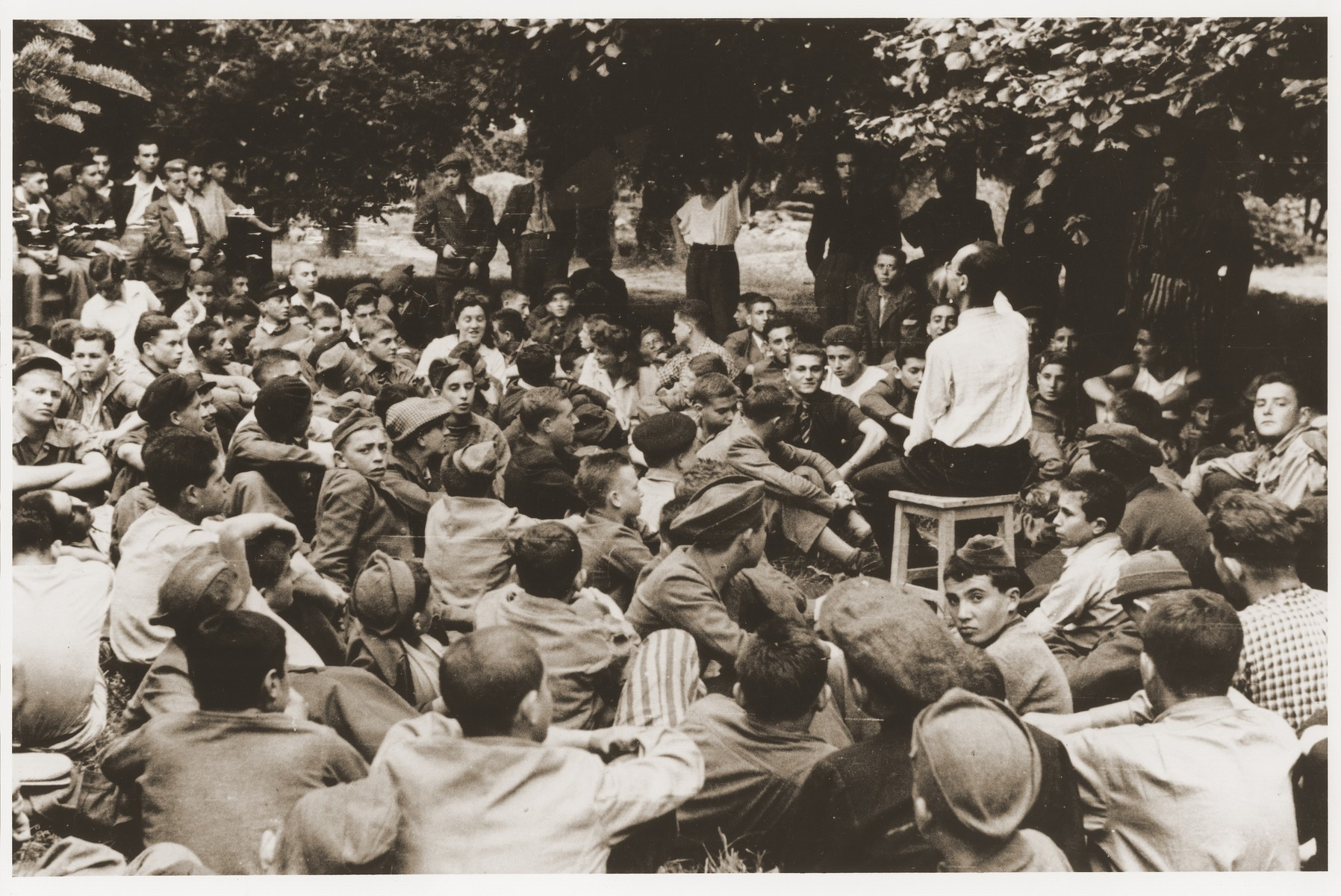 Jewish DP youth who were members of the Buchenwald children's transport listen to a speaker at an outdoor meeting at the Ecouis children's home.