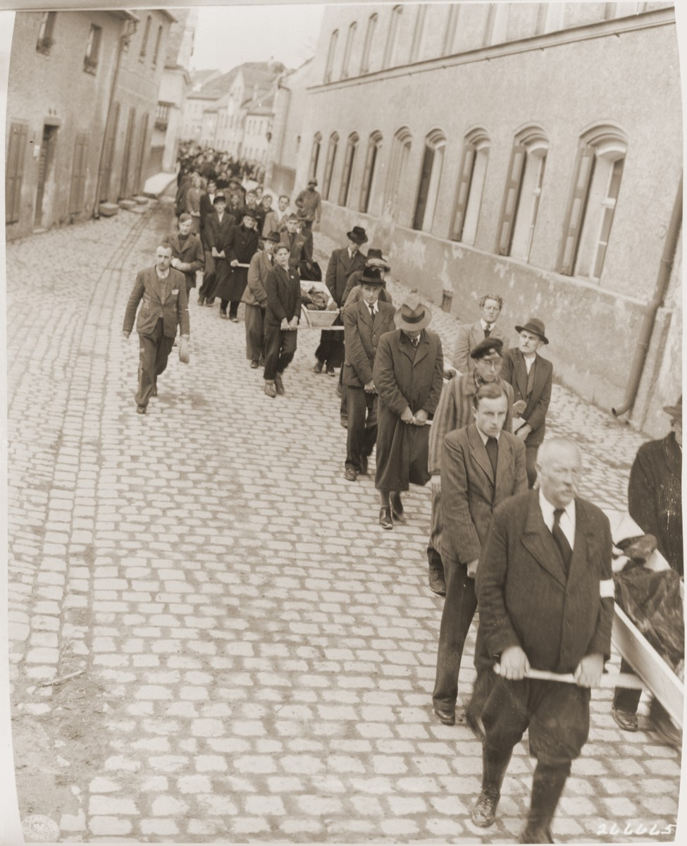 Under the supervision of American soldiers, German civilians carry wooden coffins containing the bodies of Hungarian, Russian and Polish Jews through Neunburg vorm Wald to the town cemetery for proper burial.    The victims were found in the woods near the town, where they had been shot by the SS while on a death march from Flossenbuerg.