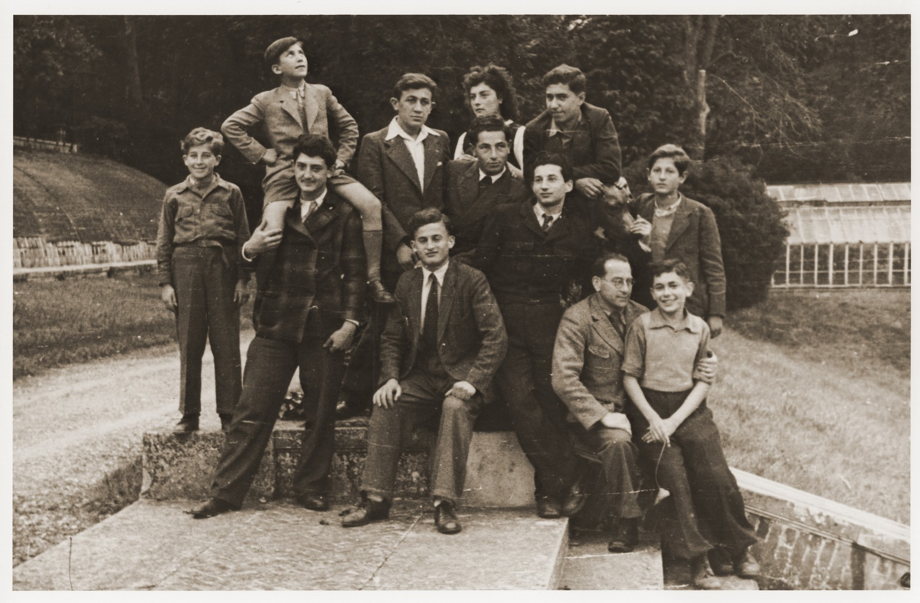 Jewish youth pose with their counselors in the yard of the Rothschild's Château Ferrière, where they are attending a summer camp sponsored by the OSE (Oeuvre de secours aux Enfants).   Pictured seated in the front row from left to right are Usher; Manfred Reingewitz and Romek Wajsman.  Standing from left to right are Abram Schilcott; Ralph Lewen with Salek Finkelstein on his shoulders; Natek Klugman; Miriam ?; Louis Harrison (in front of Miriam); Theodo (Bubi) Lowy (back, right) ; André ? (in front of Bubi-Lewi); and unknown.