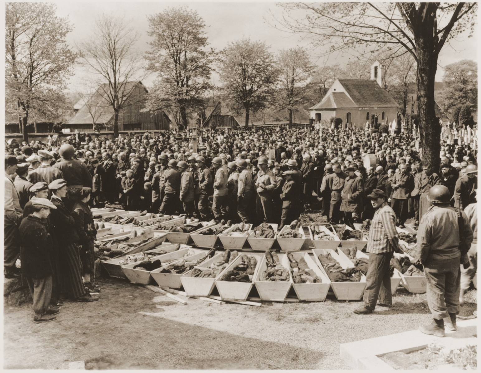U.S. troops and German civilians from Neunburg vorm Wald attend a funeral service for Polish, Hungarian, and Russian Jews found in the forest near their town.  The victims were shot by the SS while on a death march from Flossenbuerg.