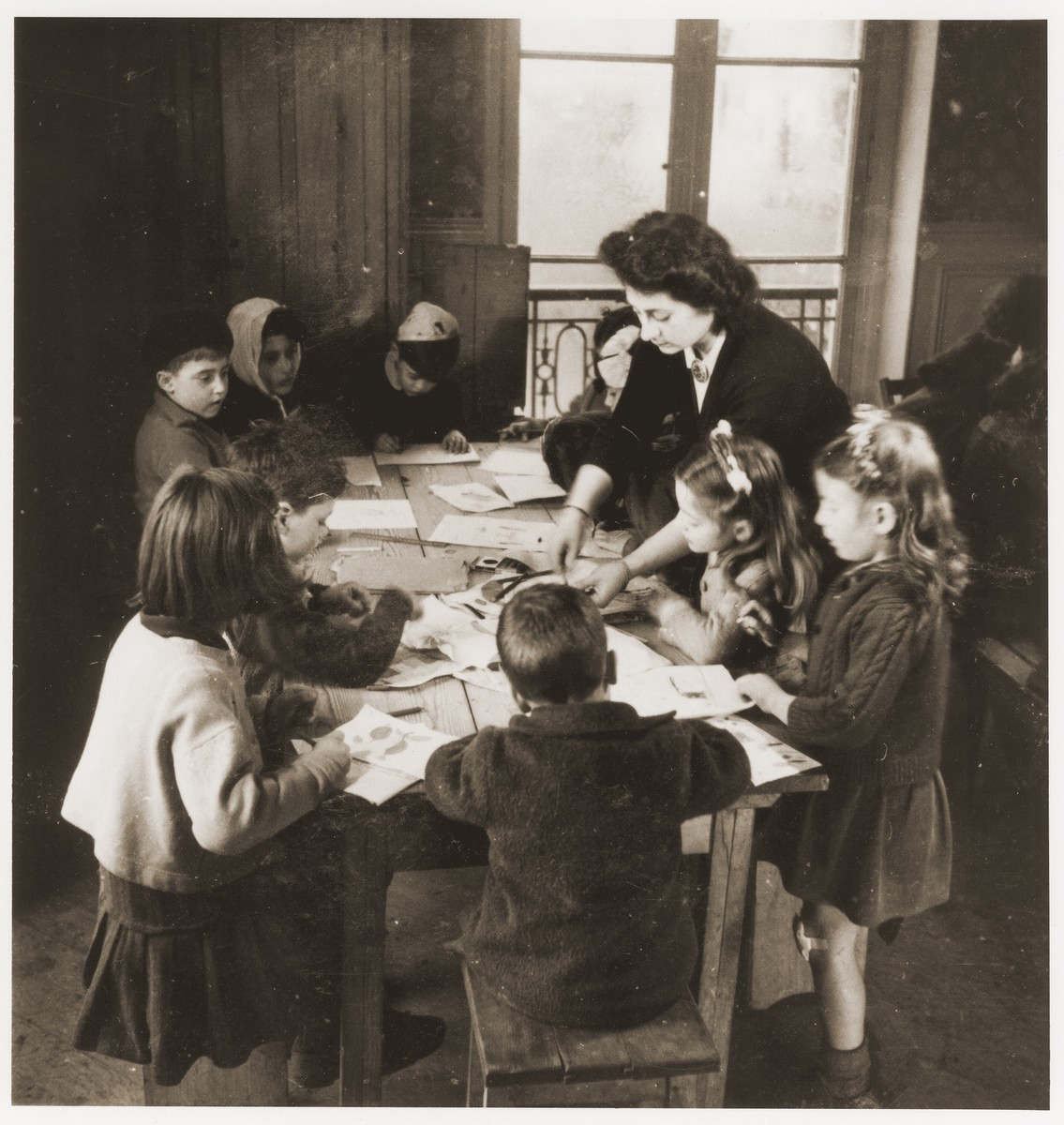 Children at the OSE children's home, Château de Vaucelles, in Taverny, sit around a table with their English teacher.    Among those pictured are Beate Zimmern (far right) and her sister, Felice (between Beate and the teacher).  Standing on the other side of the table is Leon Bretmel.