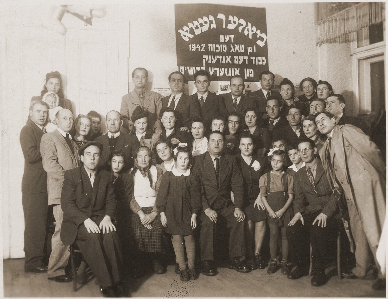 "Groups portrait of survivors of the Biala ghetto in front of a Yiddish sign that reads, ""Biala Ghetto, the first day of Sukkot 1942.  Honor to the memory of our martyrs.""  Gitta Rosenzweig is in the front row, third from right."