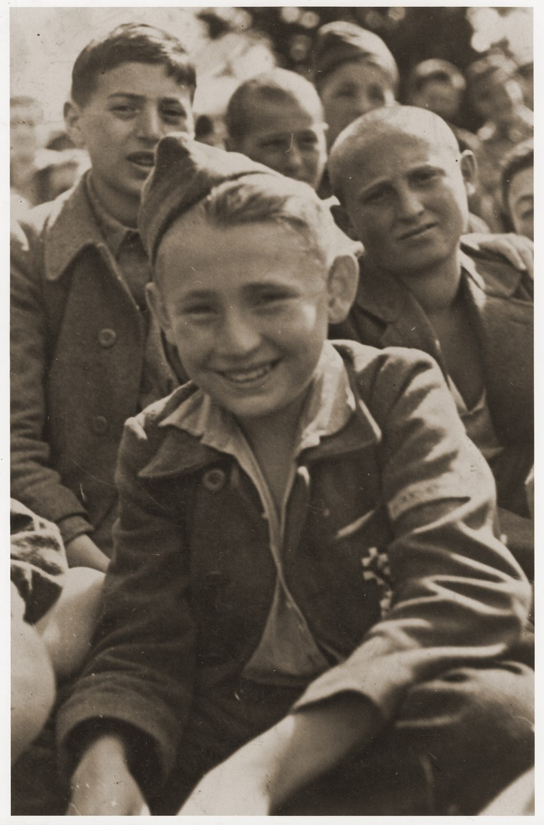 Jakub Finkelstajn sits among the members of the Buchenwald children's transport at an outdoor gathering on the grounds of the Ecouis children's home soon after their arrival.  A French military decoration is pinned to the pocket of his uniform.