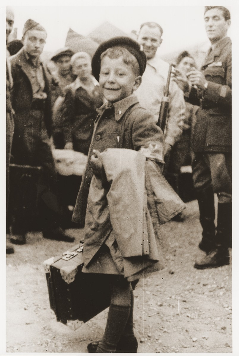 With his coat and suitcase in hand, Yisrael Meir (Lulek) Lau, a member of the Buchenwald children's transport, prepares to leave the OSE children's home in Ecouis for Palestine.