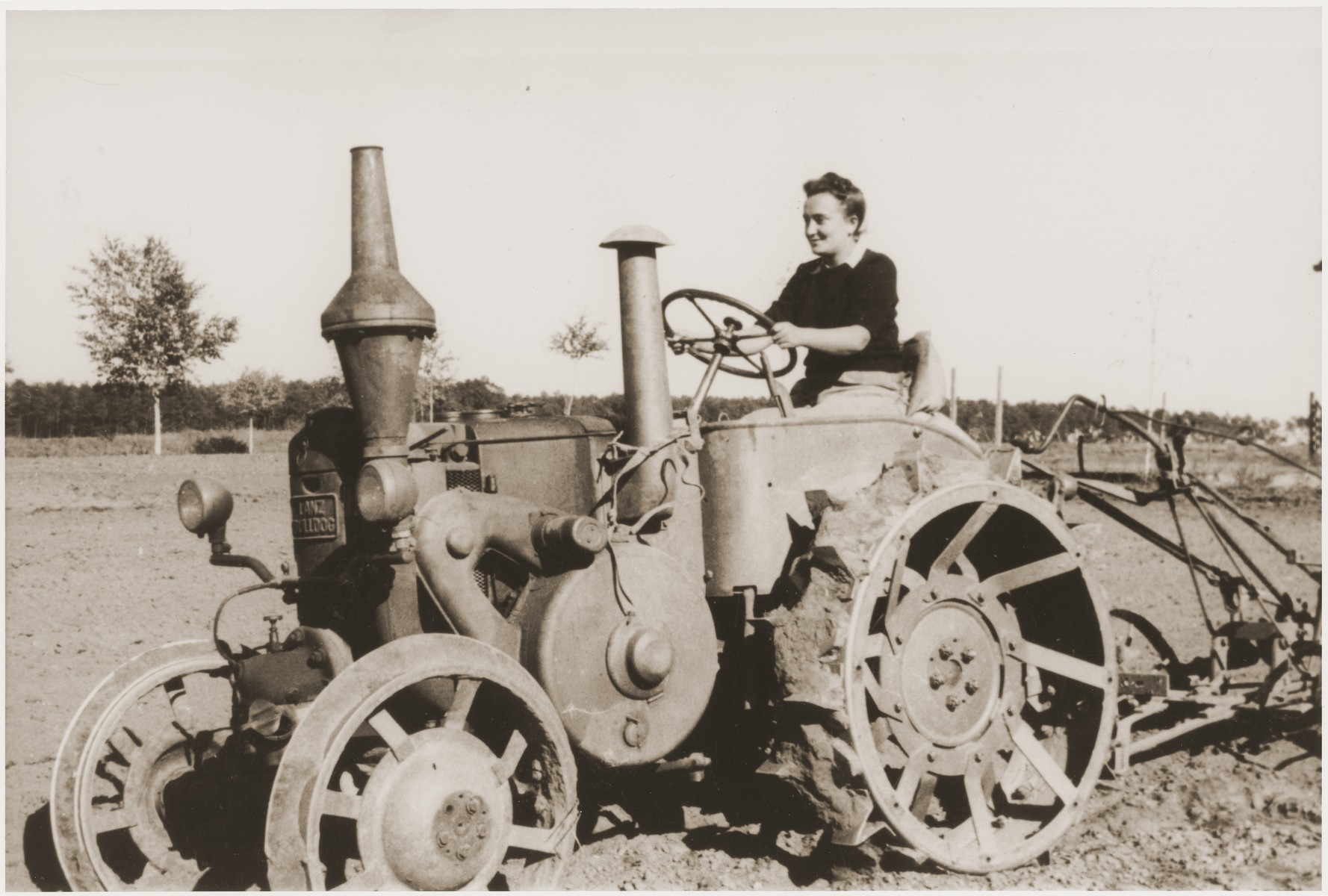 An American woman drives a tractor at the Kibbutz Nili hachshara (Zionist collective) in Pleikershof, Germany, where she came to get agricultural training.
