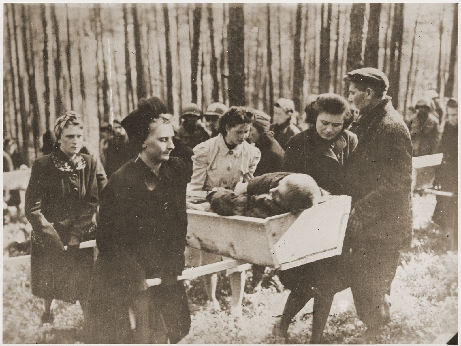 "German women transport a corpse found in the woods near Neunburg vorm Wald to the town cemetery for proper burial.  The victims were Polish, Hungarian, and Russian Jews shot near Neunburg while on a death march from Flossenbuerg.  Original caption reads, ""Civilians of Nurnburg both men and women participate in the carrying of the bodies of the slave laborers a mile and a half outside of the city of Nurnburg for burial."" [sic]"