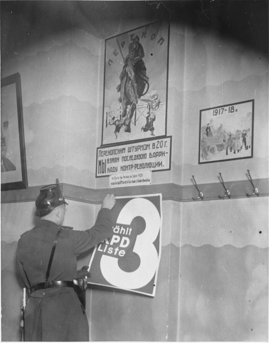 A member of the Schutzpolizei removes an election poster from a wall during the closing of the Karl-Liebknecht House (KPD headquarters), which was on the Buelowplatz in Berlin.    The closing of Communist Party offices was declared necessary for the protection of the state in the Enabling Act, passed by the Reichstag soon after the fire of 28 February 1933.