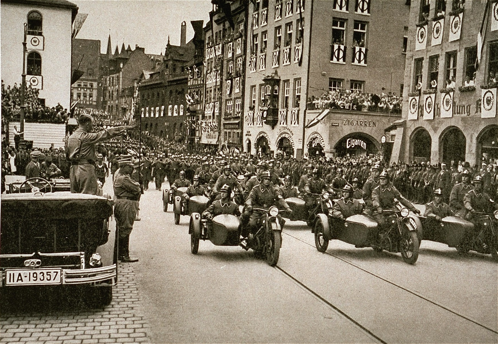 Adolf Hitler salutes a motorized SA unit from his car during a Reichsparteitag (Reich Party Day) parade.  Hermann Goering stands in front of Hitler's car.