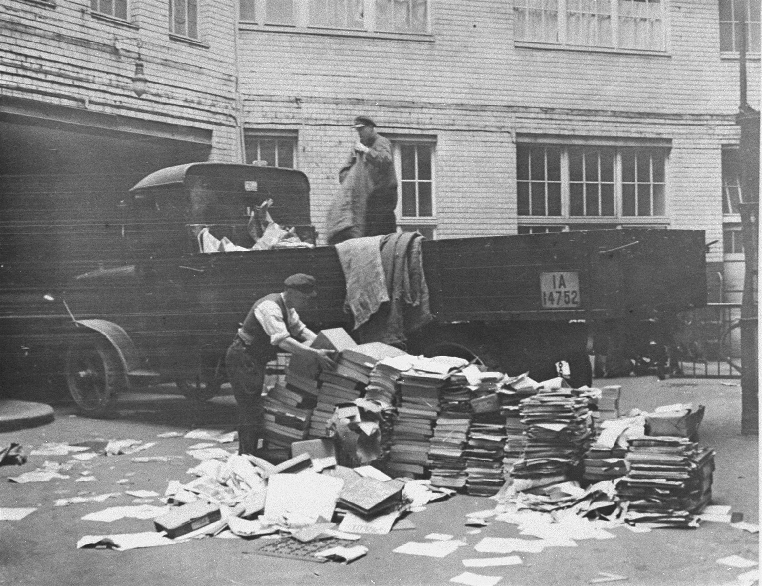 Civilians help load Communist publications onto the back of a truck during a raid of the Karl-Liebknecht House (KPD headquarters), which was on the Buelowplatz in Berlin.    The closing of Communist Party offices was declared necessary for the protection of the state in the Enabling Act, passed by the Reichstag soon after the fire of 28 February 1933.