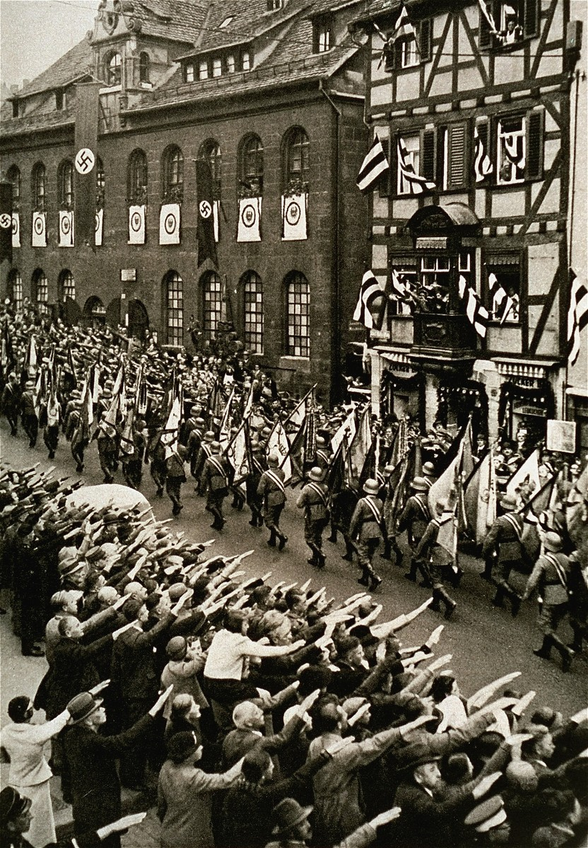 German troops parade through the streets carrying military banners during a Reichsparteitag (Reich Party Day) parade.