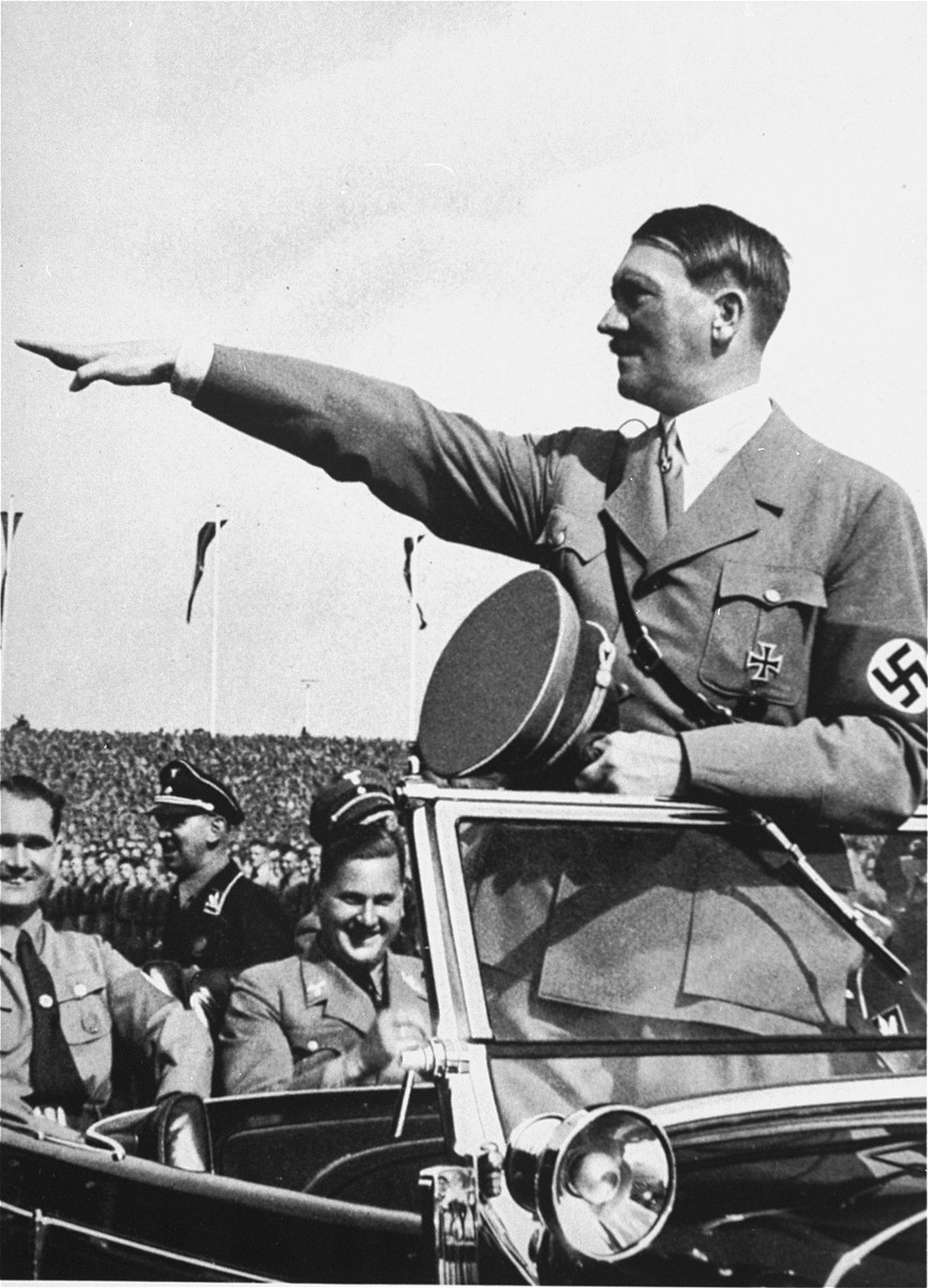 Adolf Hitler salutes the ranks of German youth from his car during a Reichsparteitag (Reich Party Day) parade.  Seated behind Hitler are Rudolf Hess (left) and Baldur von Schirach (right).