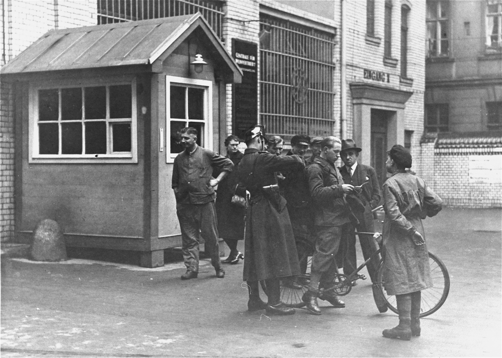 "Police search a messenger at the entrance to the building where ""Vorwaerts"", a Social-Democratic Party newspaper, was published.    The building was subsequently occupied on 4 March 1933 during the suppression of the political left-wing in Germany that was carried out in response to the Reichstag Fire."