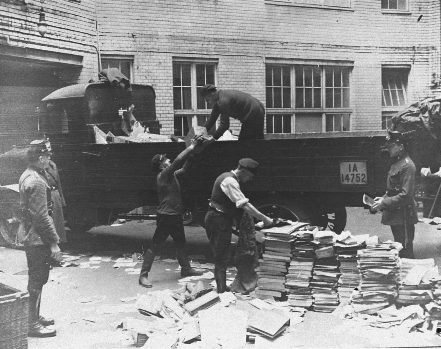Civilians load Communist publications onto the back of a truck as police look on during a raid of the Karl-Liebknecht House (KPD headquarters), which was on the Buelowplatz in Berlin.    The closing of Communist Party offices was declared necessary for the protection of the state in the Enabling Act, passed by the Reichstag soon after the fire of 28 February 1933.