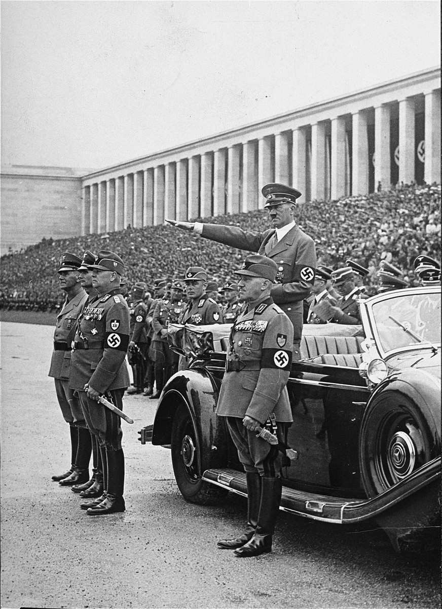 Adolf Hitler and other Nazi dignitaries observe the passage of a column of workers during Reichsparteitag (Reich Party Day) ceremonies on the Zeppelinfeld in Nuremberg.  Pictured at the far left is Wilhelm Frick.  To his left is Rudolf Hess and an unidentified RAD leader.  In the foreground is the Reichsarbeitsfuhrer, Reichsleiter Konstantin Hierl.