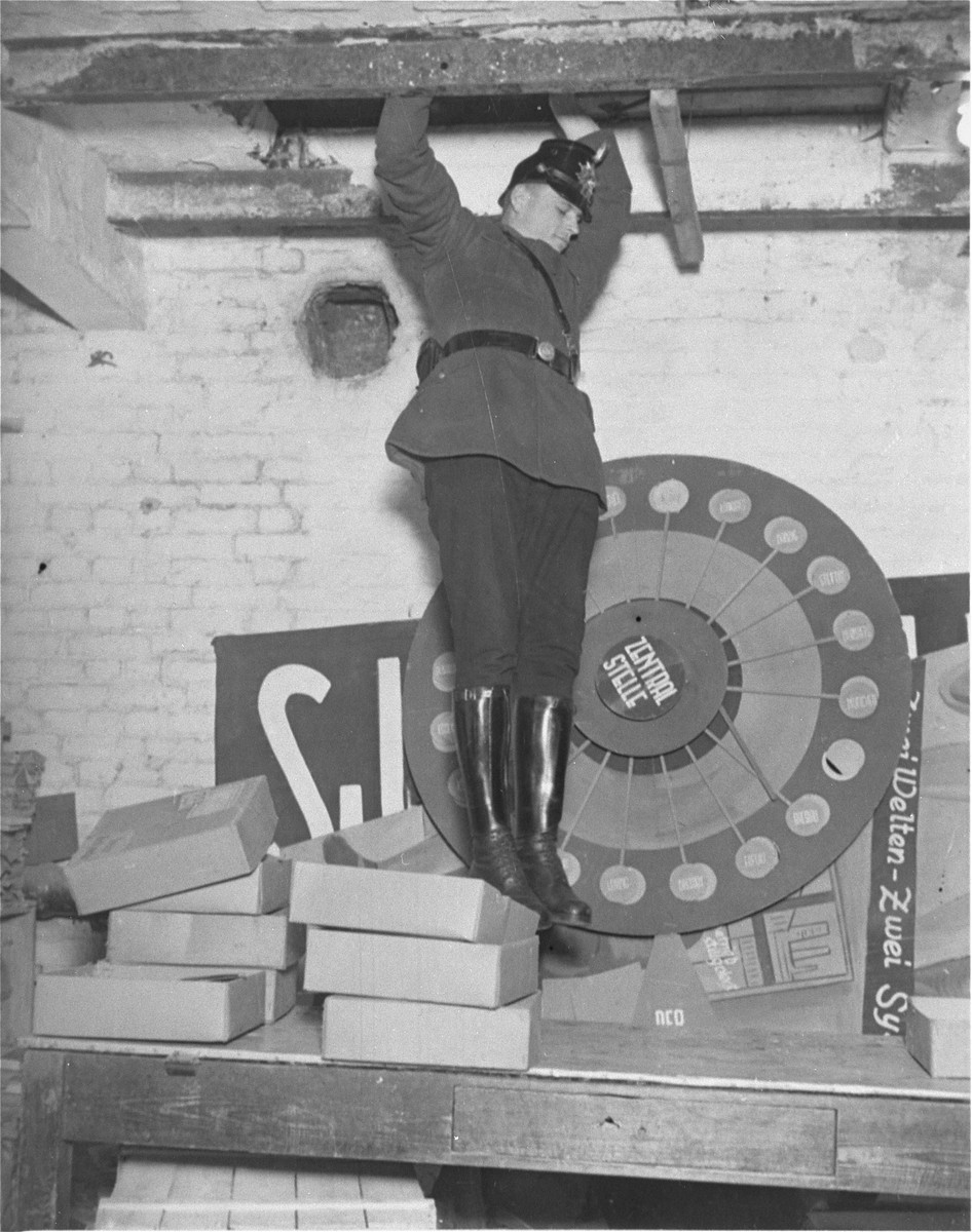 A member of the Schutzpolizei jumps down from a hole in the ceiling he searched during the closing of the Karl-Liebknecht House (KPD headquarters), which was on the Buelowplatz in Berlin.    The closing of Communist Party offices was declared necessary for the protection of the state in the Enabling Act, passed by the Reichstag soon after the fire of 28 February 1933.