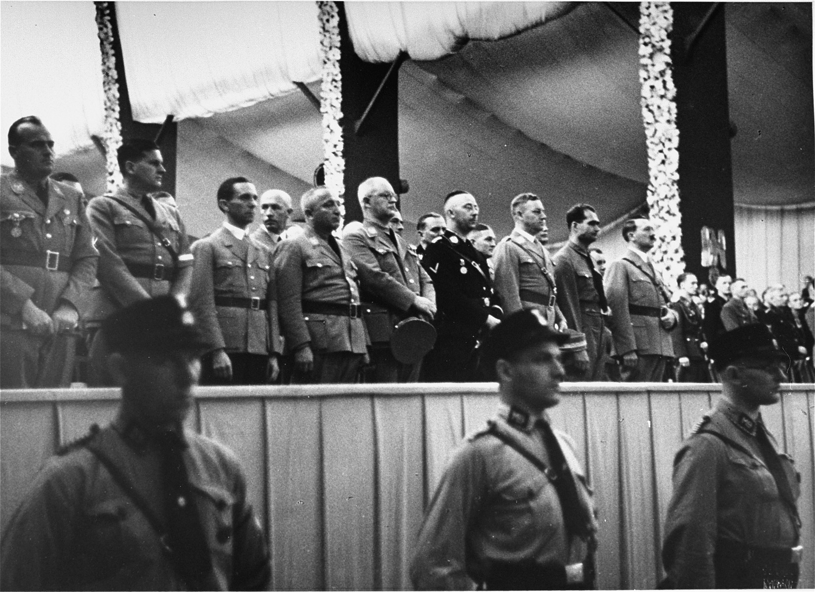 Adolf Hitler stands on a podium in the Luitpold Hall in Nuremberg with Rudolf Hess, Heinrich Himmler, and Joseph Goebbels during Reichsparteitag (Reich Party Day) ceremonies.    This image is from an SS album.