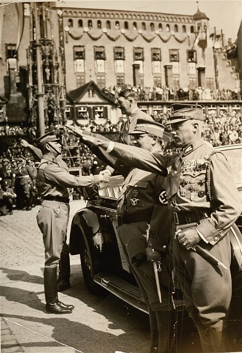 Adolf Hitler greets SA chief of staff Viktor Lutze on the Adolf Hitler Platz during Reichsparteitag (Reich Party Day) ceremonies in Nuremberg.  Pictured in the foreground is one of Lutze's predecessors as head of the SA, Franz Pfeffer von Salomon.  To Salmon's right is Hermann Goering.