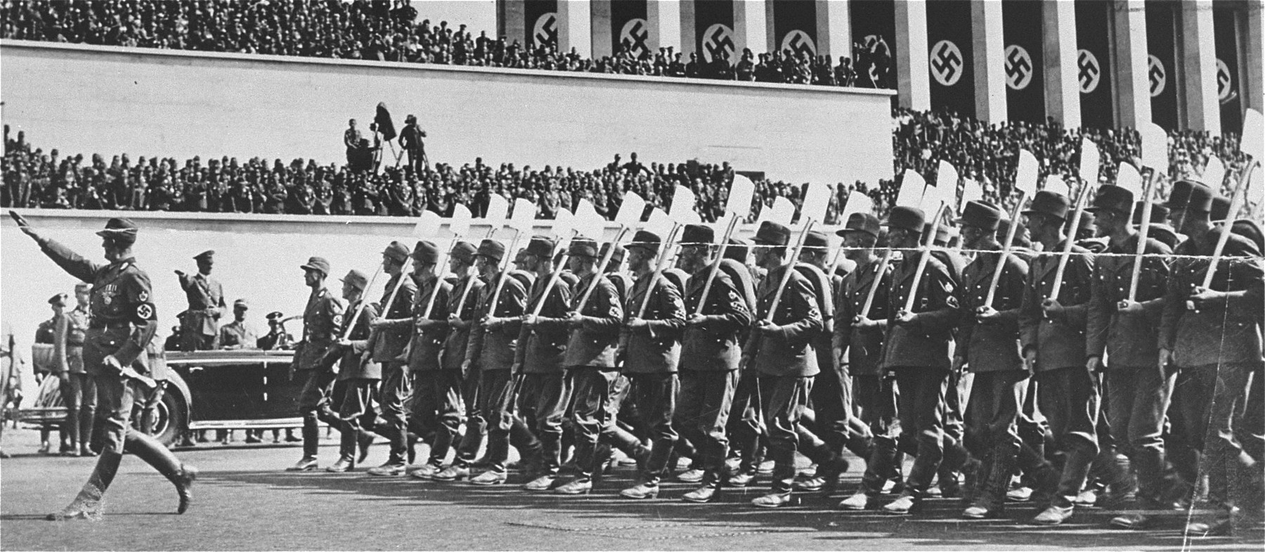 Adolf Hitler reviews units of the Reichsarbeitsdienst (RAD: Reich Labor Service) as they march past his car on the Zeppelinfeld during a Reichsparteitag (Reich Party Day) rally in Nuremberg.