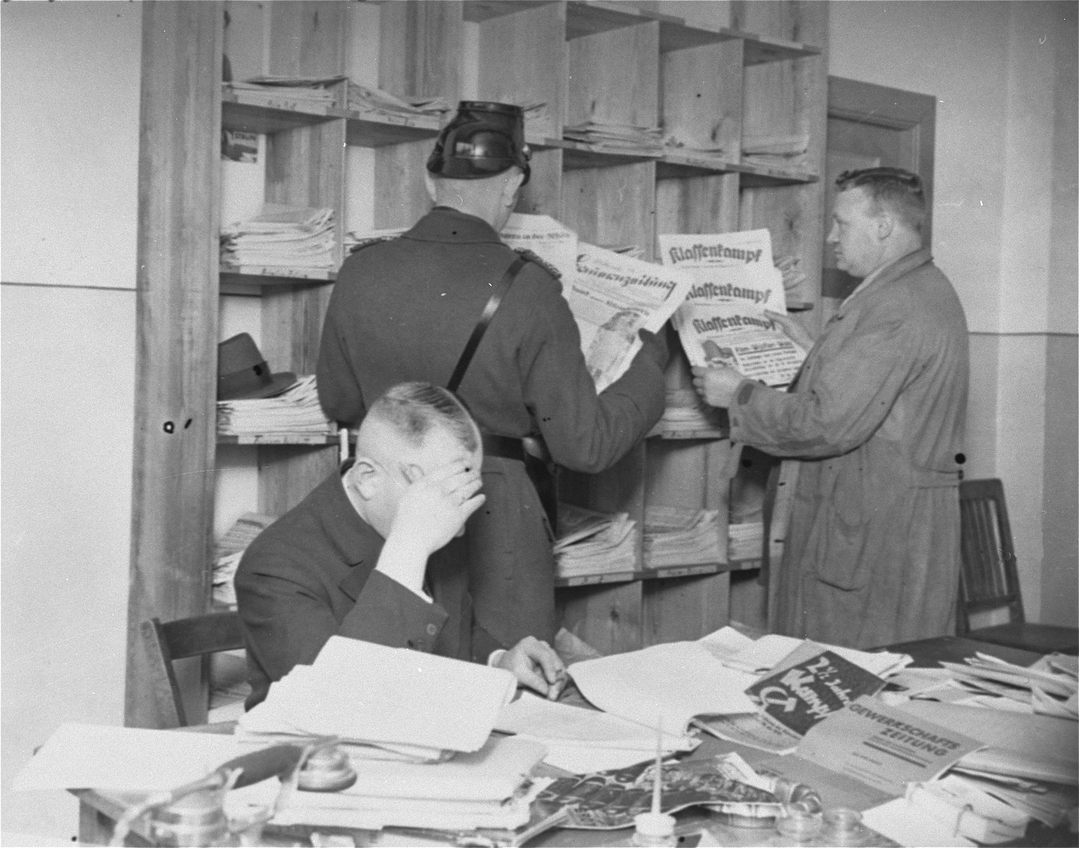Gestapo officers and a member of the Schutzpolizei look through newspapers and publications during the closing of the Karl-Liebknecht House (KPD headquarters) on the Buelowplatz in Berlin.    The closing of Communist Party offices was declared necessary for the protection of the state in the Enabling Act, passed by the Reichstag soon after the fire of 28 February 1933.