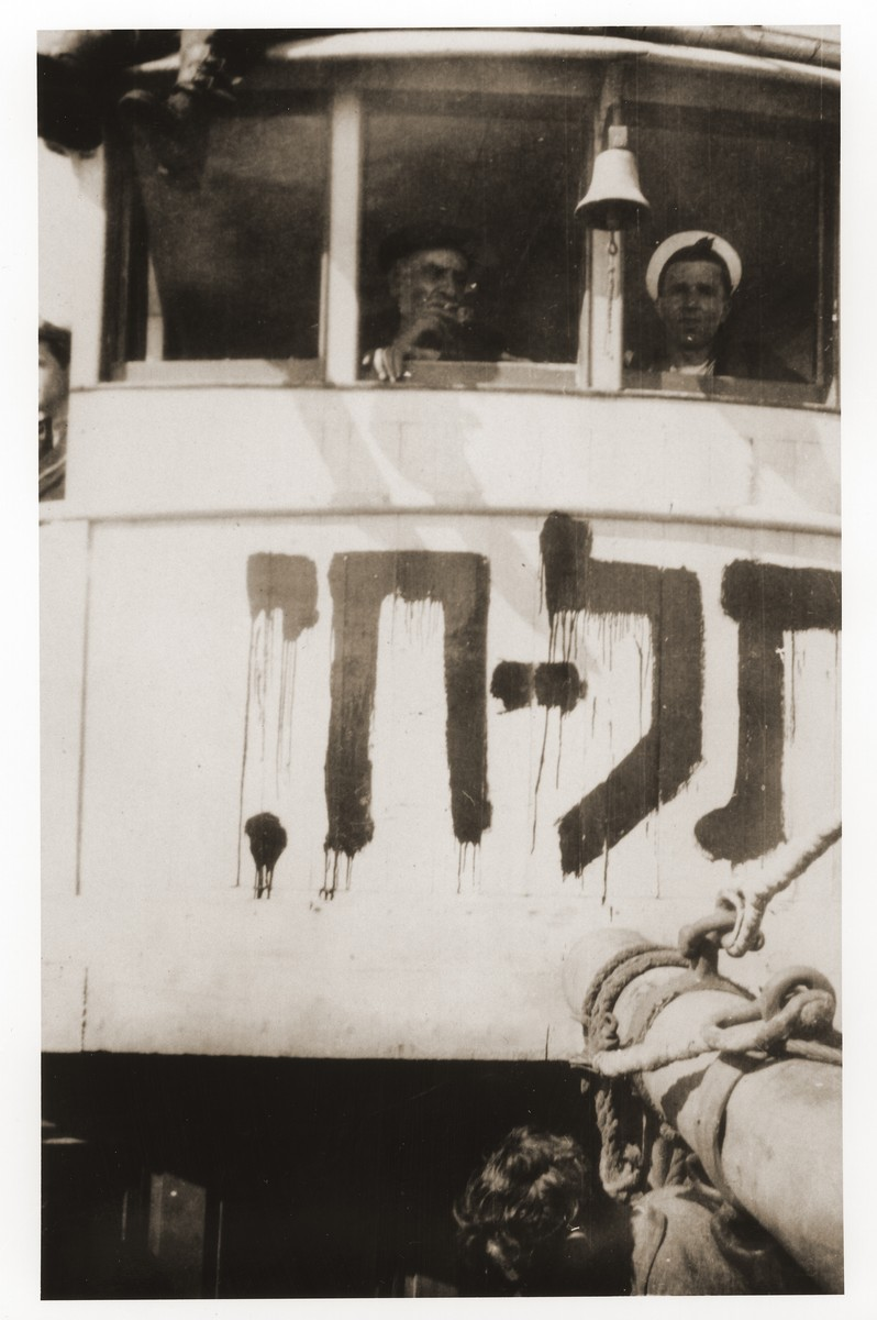 Two crew members of the Tel Hai look out the windows of their cabin.    The name of the ship has been painted directly beneath their windows.  Szaja Aron Knobler (now Alex Knobler) is the son of Moszek and Jocheta Knobler.  He was born in 1921 in Bedzin, Poland.  Szaja had three older sisters, Ita, Esther and Leah.  In 1931 the family moved to Chorzow near the German border.  There Szaja became active in the Akiba Zionist youth movement.  In 1938 he joined the Akiba hachshara [agricultural training farm] in Bielsko and made plans to immigrate to Palestine.  His plans were thwarted, however, by the start of World War II.  In the first months of the war Szaja fled to the Soviet sector of Poland, where he explored possible exit routes to Palestine via Romania for the nascent Zionist underground.  During a visit home in 1940 Szaja was caught up in the forced resettlement of his family to the Sosnowiec ghetto.  From Sosnowiec Szaja was deported to the Blechhammer labor camp, where he remained until the camp was evacuated in January 1945.  During the forced march out of the camp Szaja ran away with two friends.  German guards shot and killed his friends but Szaja escaped.  Posing as a Polish laborer, Szaja found refuge with a German farmer in Gleiwitz until liberation.  After the war Szaja, who was the sole survivor of his immediate family, took a leading role in the setting up of Zionist collectives in Poland.  He also was active in the Bricha and Aliyah Bet [illegal immigration to Palestine] movement.  This activity led to his arrest in Sosnowiec by the NKVD.  Following his release from prison, Szaja left Poland for Germany.  During the summer of 1945 Szaja organized Zionist activities at the Foehrenwald displaced persons camp.  In October he moved on to the Bergen-Belsen DP camp, where he joined a group of 400 would-be immigrants to Palestine.  The group sailed aboard the Tel Hai from Marseilles in March 1946.  When the ship reached Palestine, it was intercepted by the
