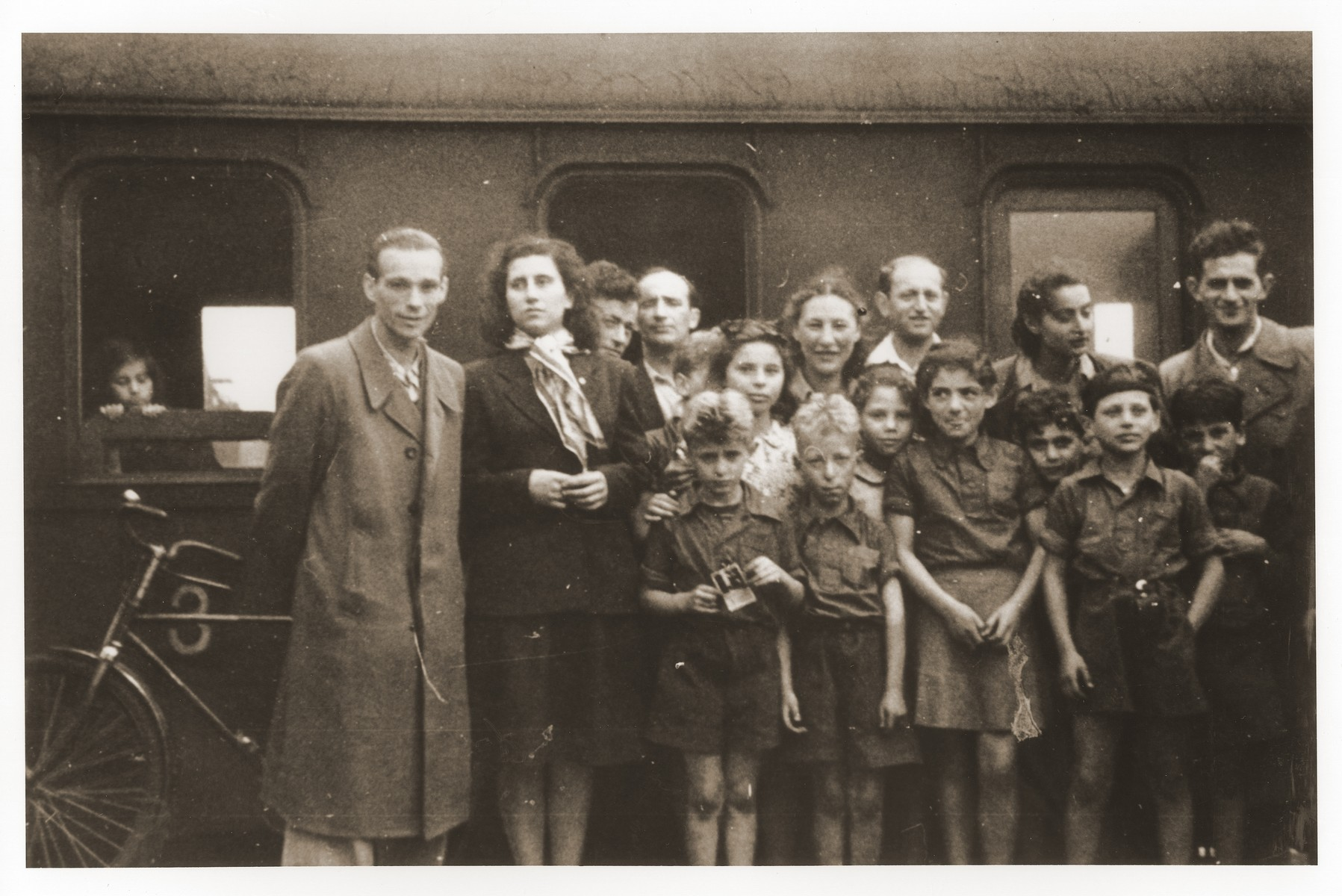 Group portrait of Youth Aliyah children from the Bergen-Belsen displaced persons camp in front of a train before their departure on the first leg of their journey to Palestine.  Szaja Aron Knobler (now Alex Knobler) is the son of Moszek and Jocheta Knobler.  He was born in 1921 in Bedzin, Poland.  Szaja had three older sisters, Ita, Esther and Leah.  In 1931 the family moved to Chorzow near the German border.  There Szaja became active in the Akiba Zionist youth movement.  In 1938 he joined the Akiba hachshara [agricultural training farm] in Bielsko and made plans to immigrate to Palestine.  His plans were thwarted, however, by the start of World War II.  In the first months of the war Szaja fled to the Soviet sector of Poland, where he explored possible exit routes to Palestine via Romania for the nascent Zionist underground.  During a visit home in 1940 Szaja was caught up in the forced resettlement of his family to the Sosnowiec ghetto.  From Sosnowiec Szaja was deported to the Blechhammer labor camp, where he remained until the camp was evacuated in January 1945.  During the forced march out of the camp Szaja ran away with two friends.  German guards shot and killed his friends but Szaja escaped.  Posing as a Polish laborer, Szaja found refuge with a German farmer in Gleiwitz until liberation.  After the war Szaja, who was the sole survivor of his immediate family, took a leading role in the setting up of Zionist collectives in Poland.  He also was active in the Bricha and Aliyah Bet [illegal immigration to Palestine] movement.  This activity led to his arrest in Sosnowiec by the NKVD.  Following his release from prison, Szaja left Poland for Germany.  During the summer of 1945 Szaja organized Zionist activities at the Foehrenwald displaced persons camp.  In October he moved on to the Bergen-Belsen DP camp, where he joined a group of 400 would-be immigrants to Palestine.  The group sailed aboard the Tel Hai from Marseilles in March 1946.  When the ship reached Palestine, it was intercepted by the British and its passengers interned for three weeks in Athlit.  Following his release Szaja settled in Kibbutz Masada, but by December 1946 he was back in Germany.  Serving as an emissary for NOHAM (Noar Halutzi Meuchad), a Zionist youth umbrella group, Szaja distributed immigration certificates and organized Youth Aliyah groups in the DP camps.  While working at the Belsen DP camp Szaja met Pola Blicblum, a survivor from Lodz.  They were married in the Landsberg DP camp on July 30, 1947.  Soon after they settled in Palestine.