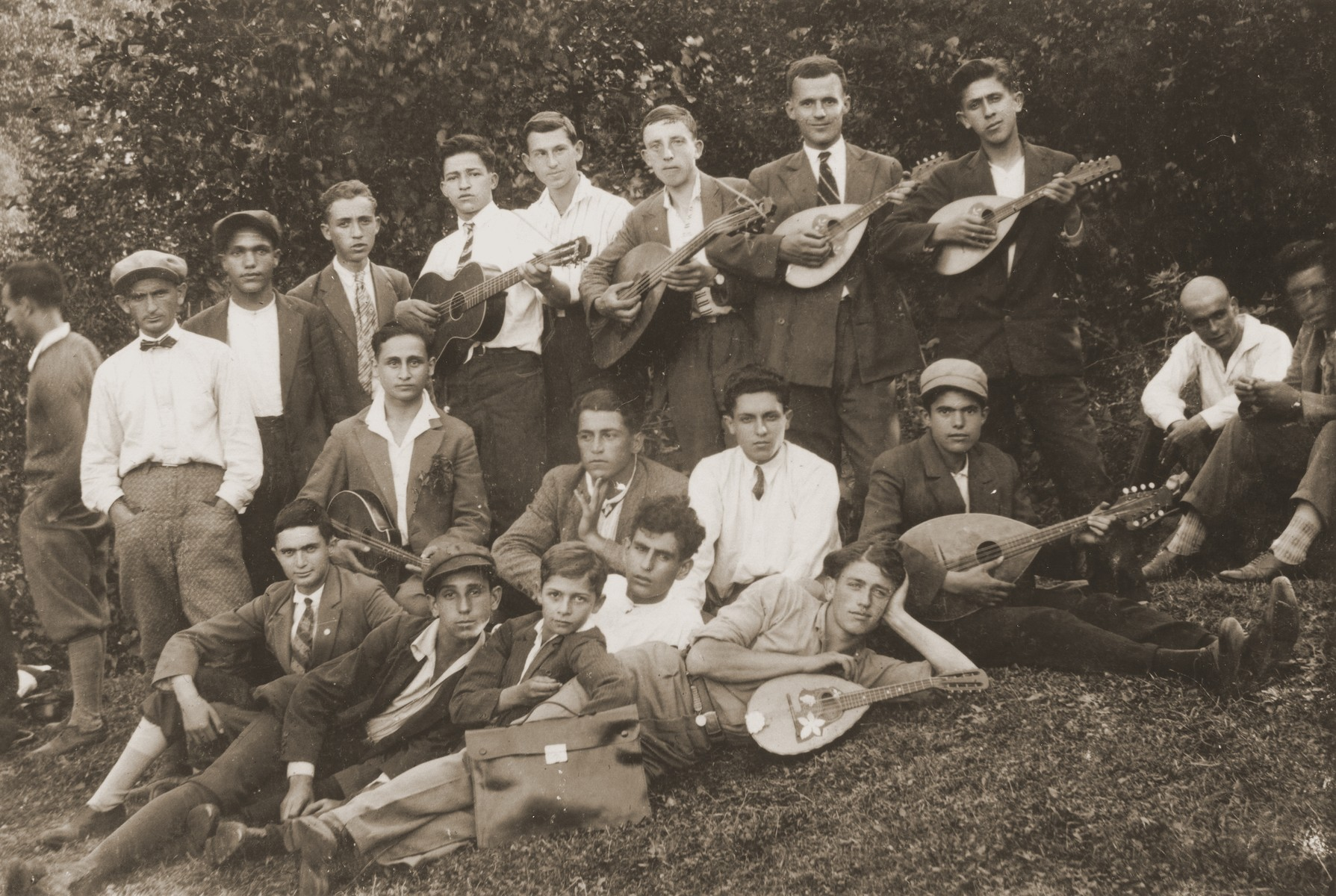 A group of Macedonian Jewish youth who are members of a mandolin band pose on a grassy hillside in Bitola, Macedonia.