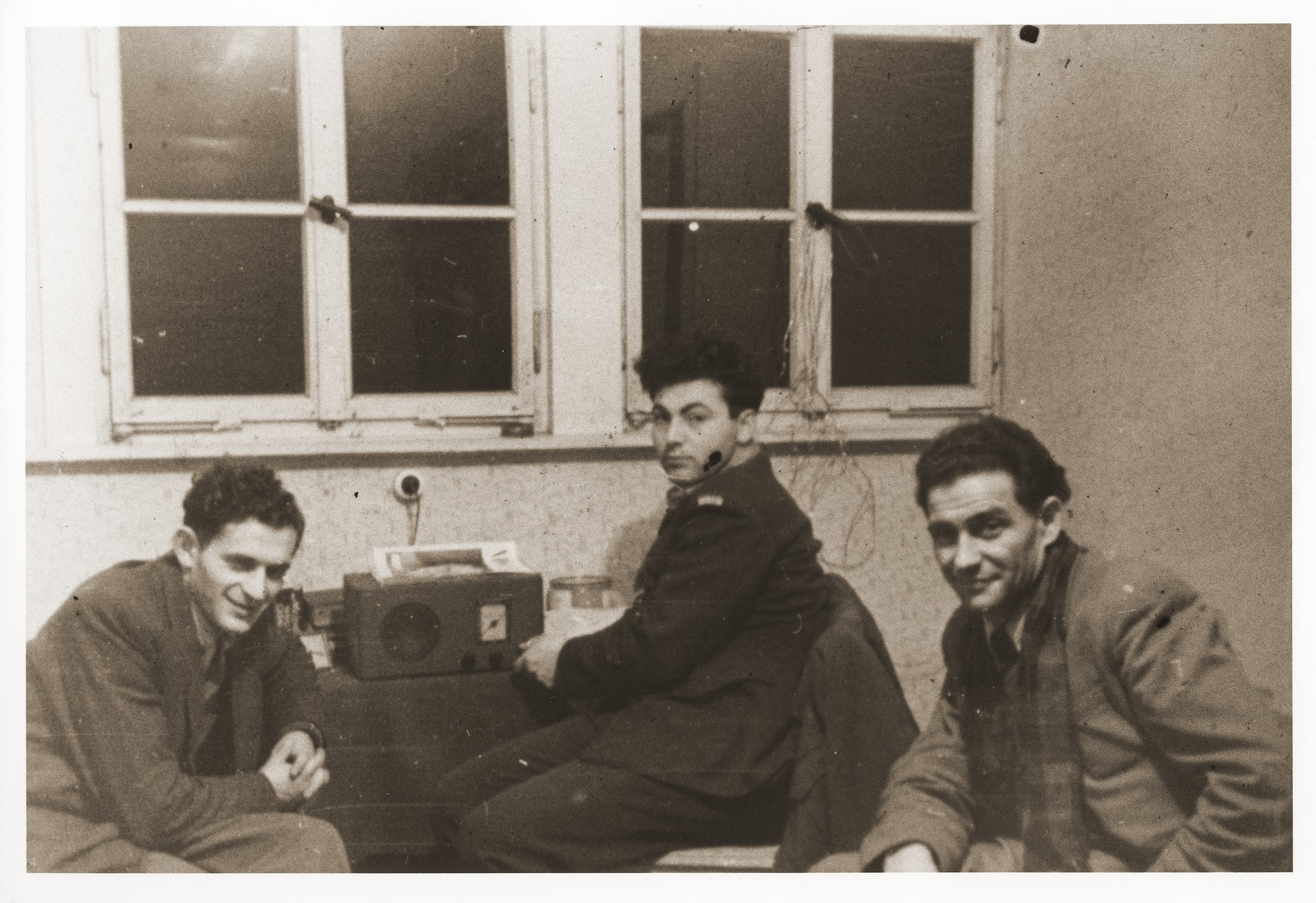 Emissaries from Palestine sent by the Haganah listen to a radio broadcast of the UN partition vote in the Bergen-Belsen displaced persons camp.  Szaja Aron Knobler (now Alex Knobler) is the son of Moszek and Jocheta Knobler.  He was born in 1921 in Bedzin, Poland.  Szaja had three older sisters, Ita, Esther and Leah.  In 1931 the family moved to Chorzow near the German border.  There Szaja became active in the Akiba Zionist youth movement.  In 1938 he joined the Akiba hachshara [agricultural training farm] in Bielsko and made plans to immigrate to Palestine.  His plans were thwarted, however, by the start of World War II.  In the first months of the war Szaja fled to the Soviet sector of Poland, where he explored possible exit routes to Palestine via Romania for the nascent Zionist underground.  During a visit home in 1940 Szaja was caught up in the forced resettlement of his family to the Sosnowiec ghetto.  From Sosnowiec Szaja was deported to the Blechhammer labor camp, where he remained until the camp was evacuated in January 1945.  During the forced march out of the camp Szaja ran away with two friends.  German guards shot and killed his friends but Szaja escaped.  Posing as a Polish laborer, Szaja found refuge with a German farmer in Gleiwitz until liberation.  After the war Szaja, who was the sole survivor of his immediate family, took a leading role in the setting up of Zionist collectives in Poland.  He also was active in the Bricha and Aliyah Bet [illegal immigration to Palestine] movement.  This activity led to his arrest in Sosnowiec by the NKVD.  Following his release from prison, Szaja left Poland for Germany.  During the summer of 1945 Szaja organized Zionist activities at the Foehrenwald displaced persons camp.  In October he moved on to the Bergen-Belsen DP camp, where he joined a group of 400 would-be immigrants to Palestine.  The group sailed aboard the Tel Hai from Marseilles in March 1946.  When the ship reached Palestine, it was intercepted by the British and its passengers interned for three weeks in Athlit.  Following his release Szaja settled in Kibbutz Masada, but by December 1946 he was back in Germany.  Serving as an emissary for NOHAM (Noar Halutzi Meuchad), a Zionist youth umbrella group, Szaja distributed immigration certificates and organized Youth Aliyah groups in the DP camps.  While working at the Belsen DP camp Szaja met Pola Blicblum, a survivor from Lodz.  They were married in the Landsberg DP camp on July 30, 1947.  Soon after they settled in Palestine.