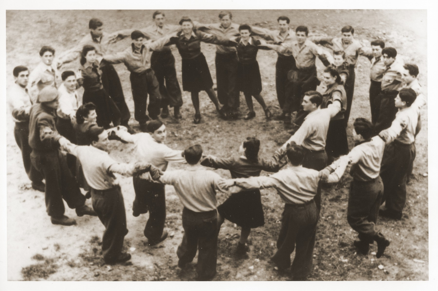 Members of the Kibbutz Hatichiya Nocham hachshara dance a hora in the Foehrenwald displaced persons camp.  Szaja Aron Knobler (now Alex Knobler) is the son of Moszek and Jocheta Knobler.  He was born in 1921 in Bedzin, Poland.  Szaja had three older sisters, Ita, Esther and Leah.  In 1931 the family moved to Chorzow near the German border.  There Szaja became active in the Akiba Zionist youth movement.  In 1938 he joined the Akiba hachshara [agricultural training farm] in Bielsko and made plans to immigrate to Palestine.  His plans were thwarted, however, by the start of World War II.  In the first months of the war Szaja fled to the Soviet sector of Poland, where he explored possible exit routes to Palestine via Romania for the nascent Zionist underground.  During a visit home in 1940 Szaja was caught up in the forced resettlement of his family to the Sosnowiec ghetto.  From Sosnowiec Szaja was deported to the Blechhammer labor camp, where he remained until the camp was evacuated in January 1945.  During the forced march out of the camp Szaja ran away with two friends.  German guards shot and killed his friends but Szaja escaped.  Posing as a Polish laborer, Szaja found refuge with a German farmer in Gleiwitz until liberation.  After the war Szaja, who was the sole survivor of his immediate family, took a leading role in the setting up of Zionist collectives in Poland.  He also was active in the Bricha and Aliyah Bet [illegal immigration to Palestine] movement.  This activity led to his arrest in Sosnowiec by the NKVD.  Following his release from prison, Szaja left Poland for Germany.  During the summer of 1945 Szaja organized Zionist activities at the Foehrenwald displaced persons camp.  In October he moved on to the Bergen-Belsen DP camp, where he joined a group of 400 would-be immigrants to Palestine.  The group sailed aboard the Tel Hai from Marseilles in March 1946.  When the ship reached Palestine, it was intercepted by the British and its passengers interned