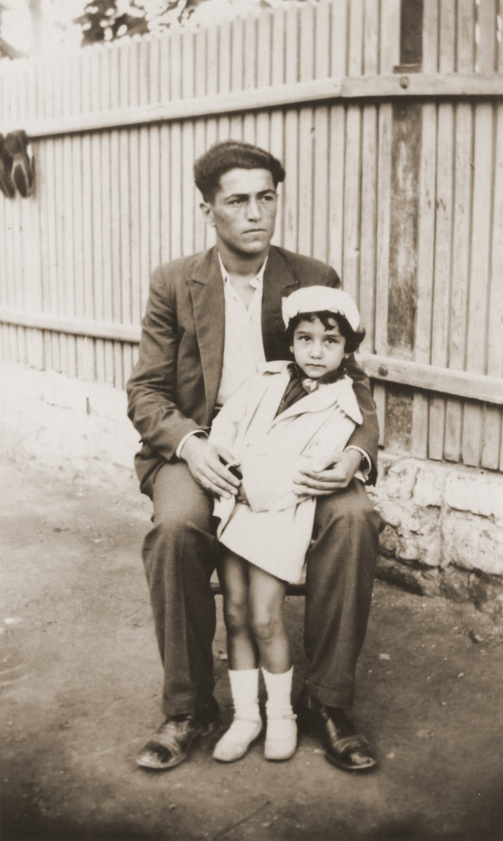 Portrait of a young man holding a little girl in front of a fence.