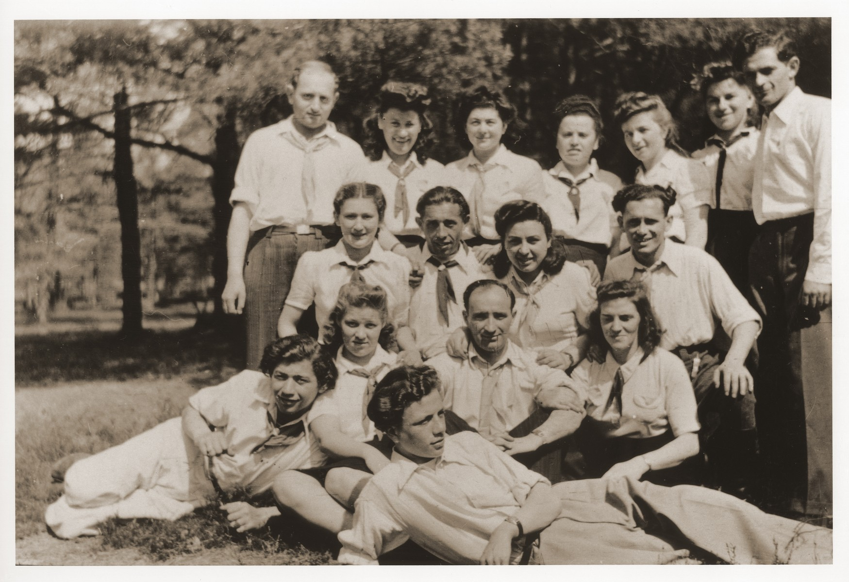 Group portrait of members of Kibbutz Nocham in the Bergen-Belsen displaced persons camp.  Szaja Aron Knobler (now Alex Knobler) is the son of Moszek and Jocheta Knobler.  He was born in 1921 in Bedzin, Poland.  Szaja had three older sisters, Ita, Esther and Leah.  In 1931 the family moved to Chorzow near the German border.  There Szaja became active in the Akiba Zionist youth movement.  In 1938 he joined the Akiba hachshara [agricultural training farm] in Bielsko and made plans to immigrate to Palestine.  His plans were thwarted, however, by the start of World War II.  In the first months of the war Szaja fled to the Soviet sector of Poland, where he explored possible exit routes to Palestine via Romania for the nascent Zionist underground.  During a visit home in 1940 Szaja was caught up in the forced resettlement of his family to the Sosnowiec ghetto.  From Sosnowiec Szaja was deported to the Blechhammer labor camp, where he remained until the camp was evacuated in January 1945.  During the forced march out of the camp Szaja ran away with two friends.  German guards shot and killed his friends but Szaja escaped.  Posing as a Polish laborer, Szaja found refuge with a German farmer in Gleiwitz until liberation.  After the war Szaja, who was the sole survivor of his immediate family, took a leading role in the setting up of Zionist collectives in Poland.  He also was active in the Bricha and Aliyah Bet [illegal immigration to Palestine] movement.  This activity led to his arrest in Sosnowiec by the NKVD.  Following his release from prison, Szaja left Poland for Germany.  During the summer of 1945 Szaja organized Zionist activities at the Foehrenwald displaced persons camp.  In October he moved on to the Bergen-Belsen DP camp, where he joined a group of 400 would-be immigrants to Palestine.  The group sailed aboard the Tel Hai from Marseilles in March 1946.  When the ship reached Palestine, it was intercepted by the British and its passengers interned for three weeks 