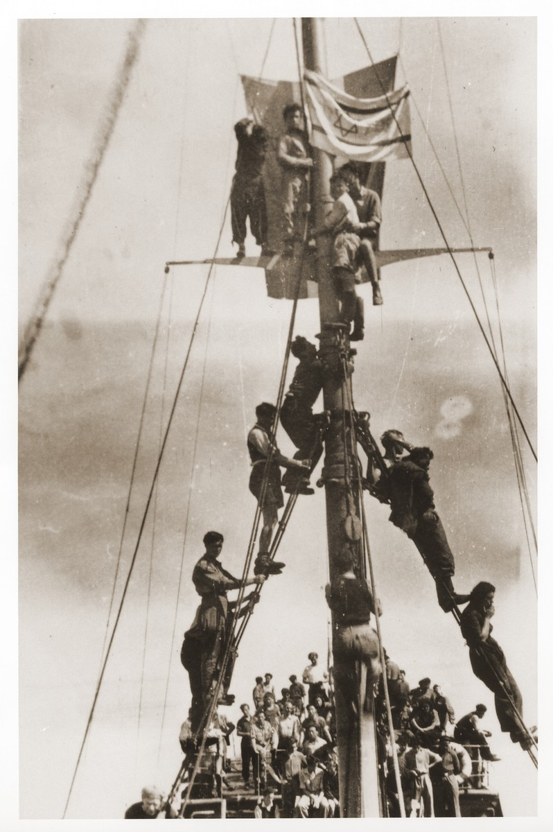 Illegal immigrants sailing to Palestine aboard the Tel Hai, climb the mast of the ship to hoist the Zionist flag.  Szaja Aron Knobler (now Alex Knobler) is the son of Moszek and Jocheta Knobler.  He was born in 1921 in Bedzin, Poland.  Szaja had three older sisters, Ita, Esther and Leah.  In 1931 the family moved to Chorzow near the German border.  There Szaja became active in the Akiba Zionist youth movement.  In 1938 he joined the Akiba hachshara [agricultural training farm] in Bielsko and made plans to immigrate to Palestine.  His plans were thwarted, however, by the start of World War II.  In the first months of the war Szaja fled to the Soviet sector of Poland, where he explored possible exit routes to Palestine via Romania for the nascent Zionist underground.  During a visit home in 1940 Szaja was caught up in the forced resettlement of his family to the Sosnowiec ghetto.  From Sosnowiec Szaja was deported to the Blechhammer labor camp, where he remained until the camp was evacuated in January 1945.  During the forced march out of the camp Szaja ran away with two friends.  German guards shot and killed his friends but Szaja escaped.  Posing as a Polish laborer, Szaja found refuge with a German farmer in Gleiwitz until liberation.  After the war Szaja, who was the sole survivor of his immediate family, took a leading role in the setting up of Zionist collectives in Poland.  He also was active in the Bricha and Aliyah Bet [illegal immigration to Palestine] movement.  This activity led to his arrest in Sosnowiec by the NKVD.  Following his release from prison, Szaja left Poland for Germany.  During the summer of 1945 Szaja organized Zionist activities at the Foehrenwald displaced persons camp.  In October he moved on to the Bergen-Belsen DP camp, where he joined a group of 400 would-be immigrants to Palestine.  The group sailed aboard the Tel Hai from Marseilles in March 1946.  When the ship reached Palestine, it was intercepted by the British and its passengers interned for three weeks in Athlit.  Following his release Szaja settled in Kibbutz Masada, but by December 1946 he was back in Germany.  Serving as an emissary for NOHAM (Noar Halutzi Meuchad), a Zionist youth umbrella group, Szaja distributed immigration certificates and organized Youth Aliyah groups in the DP camps.  While working at the Belsen DP camp Szaja met Pola Blicblum, a survivor from Lodz.  They were married in the Landsberg DP camp on July 30, 1947.  Soon after they settled in Palestine.