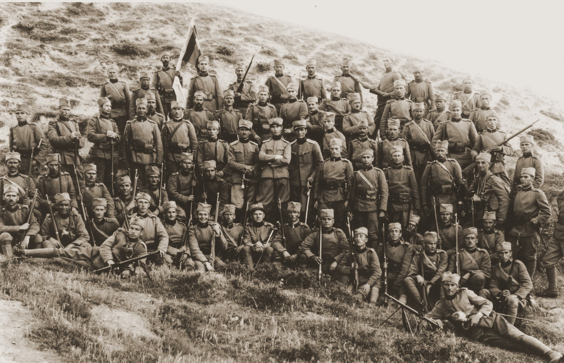 A Yugoslav military unit that included Jewish recruits, poses on a barren hillside.
