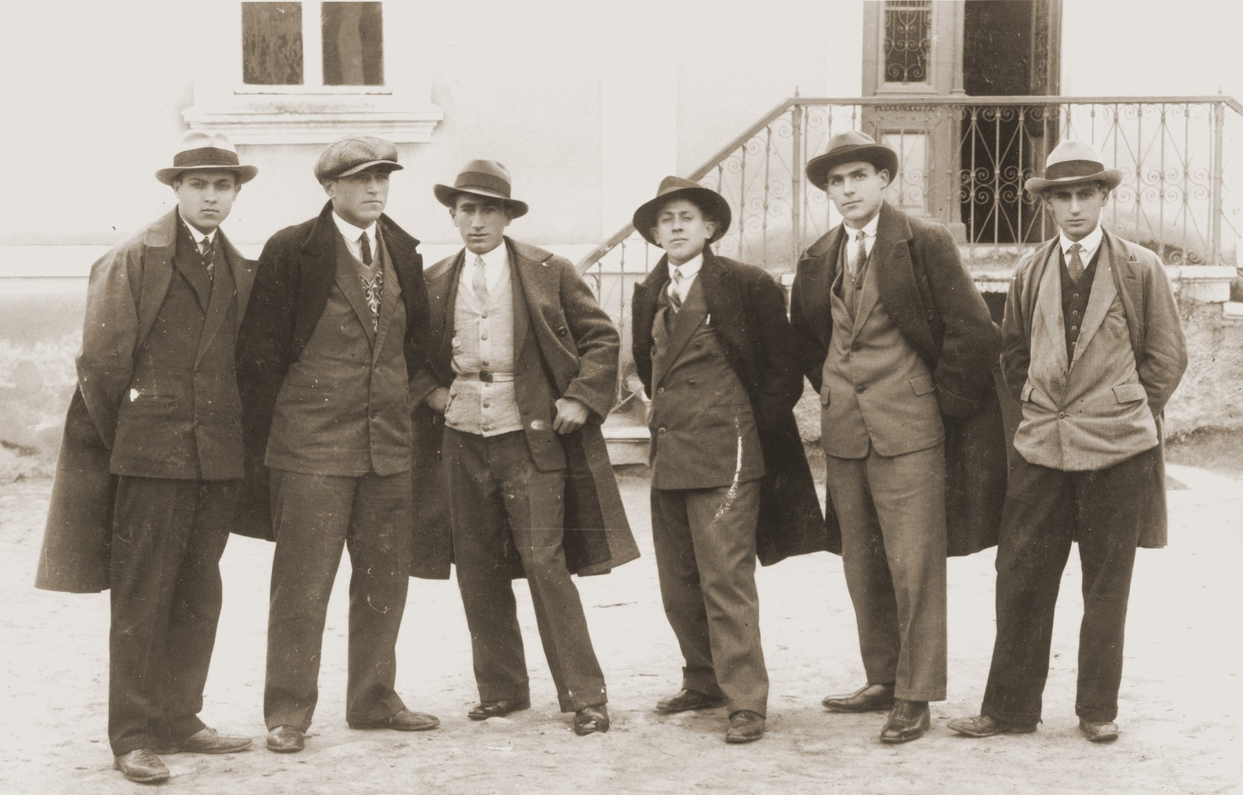 A group of young Jewish men in jackets and ties pose outside a building in Bitola, Macedonia.