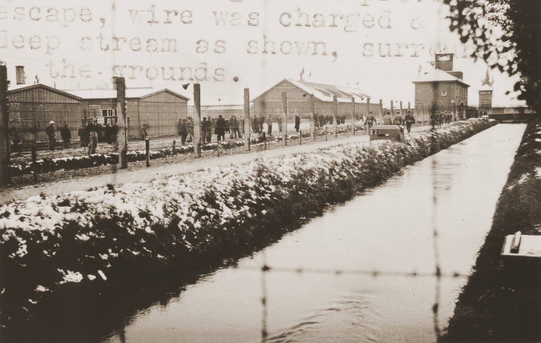 View of the newly liberated Dachau concentration camp, in which survivors are walking along the main street of the camp behind a long, barbed-wire fence that runs parallel to a moat