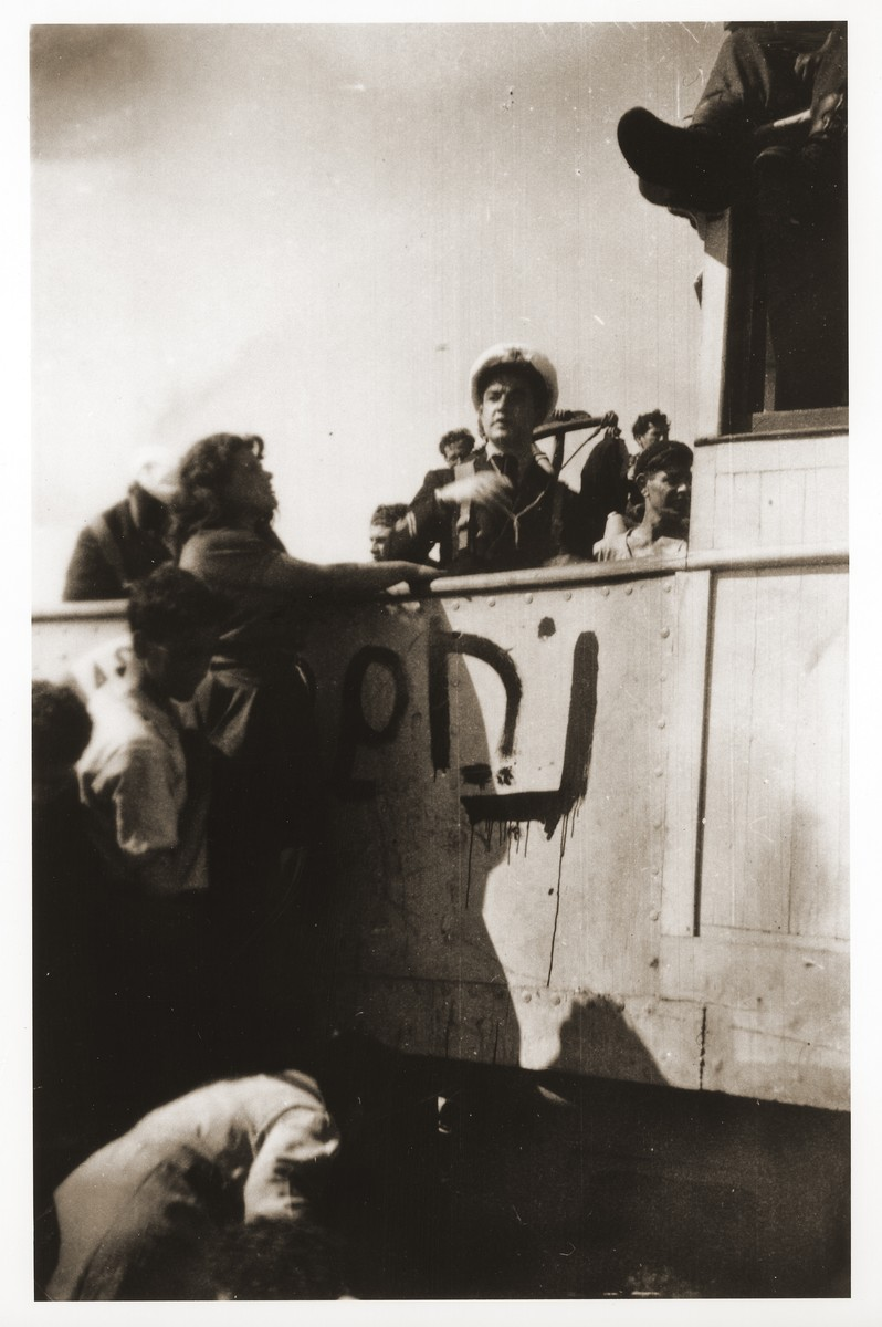 "The captain of the Tel Hai talks to illegal immigrants on board the ship.    Printed beneath him on the wall of the ship is the Hebrew work ""Noham,"" an acronym for the Zionist youth movement to which this group belonged.  Szaja Aron Knobler (now Alex Knobler) is the son of Moszek and Jocheta Knobler.  He was born in 1921 in Bedzin, Poland.  Szaja had three older sisters, Ita, Esther and Leah.  In 1931 the family moved to Chorzow near the German border.  There Szaja became active in the Akiba Zionist youth movement.  In 1938 he joined the Akiba hachshara [agricultural training farm] in Bielsko and made plans to immigrate to Palestine.  His plans were thwarted, however, by the start of World War II.  In the first months of the war Szaja fled to the Soviet sector of Poland, where he explored possible exit routes to Palestine via Romania for the nascent Zionist underground.  During a visit home in 1940 Szaja was caught up in the forced resettlement of his family to the Sosnowiec ghetto.  From Sosnowiec Szaja was deported to the Blechhammer labor camp, where he remained until the camp was evacuated in January 1945.  During the forced march out of the camp Szaja ran away with two friends.  German guards shot and killed his friends but Szaja escaped.  Posing as a Polish laborer, Szaja found refuge with a German farmer in Gleiwitz until liberation.  After the war Szaja, who was the sole survivor of his immediate family, took a leading role in the setting up of Zionist collectives in Poland.  He also was active in the Bricha and Aliyah Bet [illegal immigration to Palestine] movement.  This activity led to his arrest in Sosnowiec by the NKVD.  Following his release from prison, Szaja left Poland for Germany.  During the summer of 1945 Szaja organized Zionist activities at the Foehrenwald displaced persons camp.  In October he moved on to the Bergen-Belsen DP camp, where he joined a group of 400 would-be immigrants to Palestine.  The group sailed aboard the Tel Hai from Marseilles in March 1946.  When the ship reached Palestine, it was intercepted by the British and its passengers interned for three weeks in Athlit.  Following his release Szaja settled in Kibbutz Masada, but by December 1946 he was back in Germany.  Serving as an emissary for NOHAM (Noar Halutzi Meuchad), a Zionist youth umbrella group, Szaja distributed immigration certificates and organized Youth Aliyah groups in the DP camps.  While working at the Belsen DP camp Szaja met Pola Blicblum, a survivor from Lodz.  They were married in the Landsberg DP camp on July 30, 1947.  Soon after they settled in Palestine."