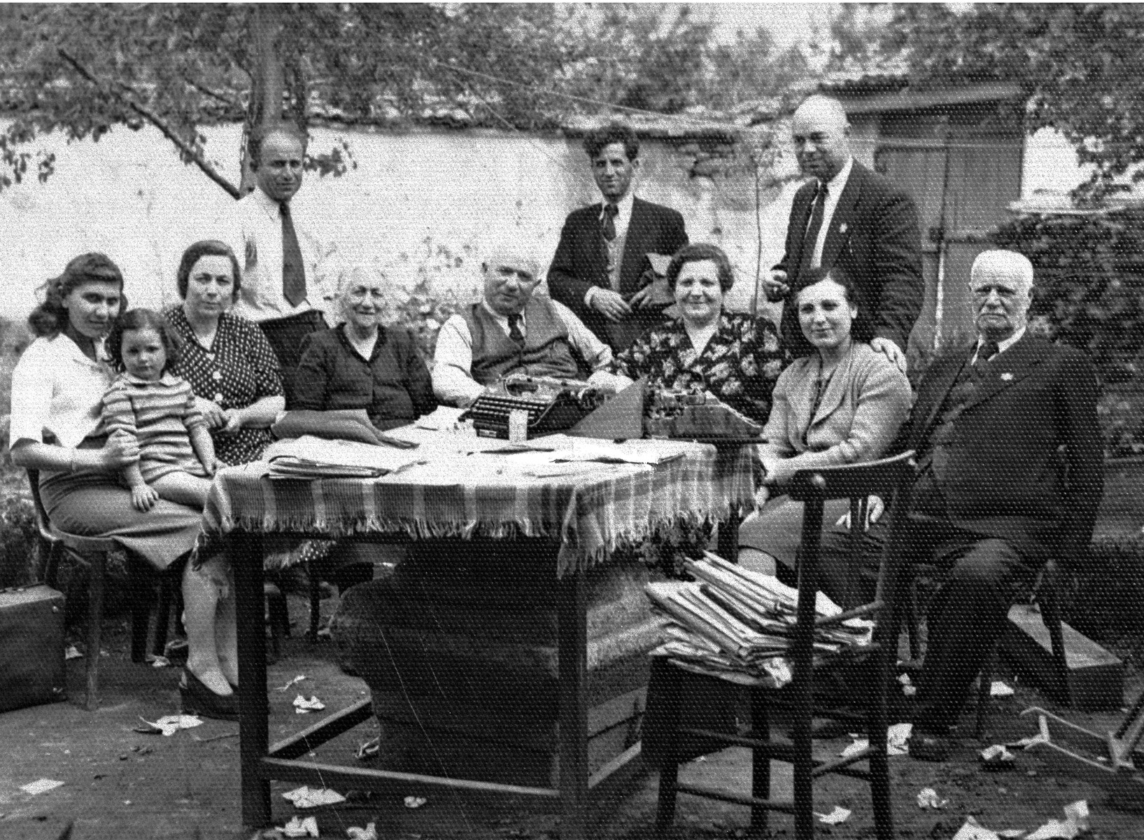 Members of the extended Baruch family pose outside around a table in the yard of their residence in Kyustendil, Bulgaria, following their expulsion from the capital, Sofia.  During the period of their exile in the provinces, the members of extended Baruch family lived in the home of Miriam and Pinkas Baruch, who had retained their house in Kyustendil after moving to Sofia in the 1930s.