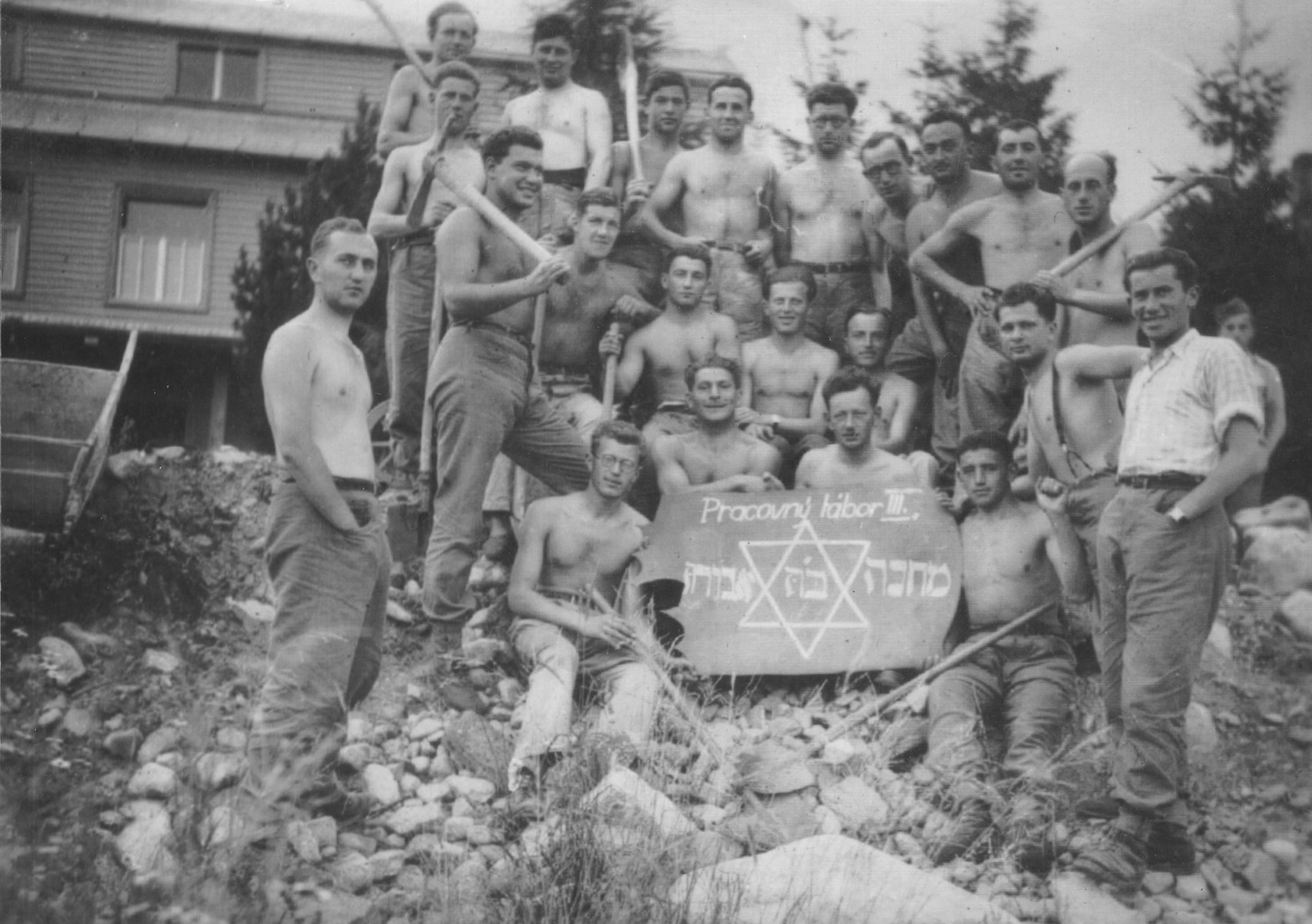 Jewish graduates of a military officers' school pose with a sign in a labor camp in the High Tatras.    Those who had already been commissioned as officers lost their military ranks.  Alexander Bachner is probably standing on the right.  Ernest Neustadt is in the top row, third from the right.