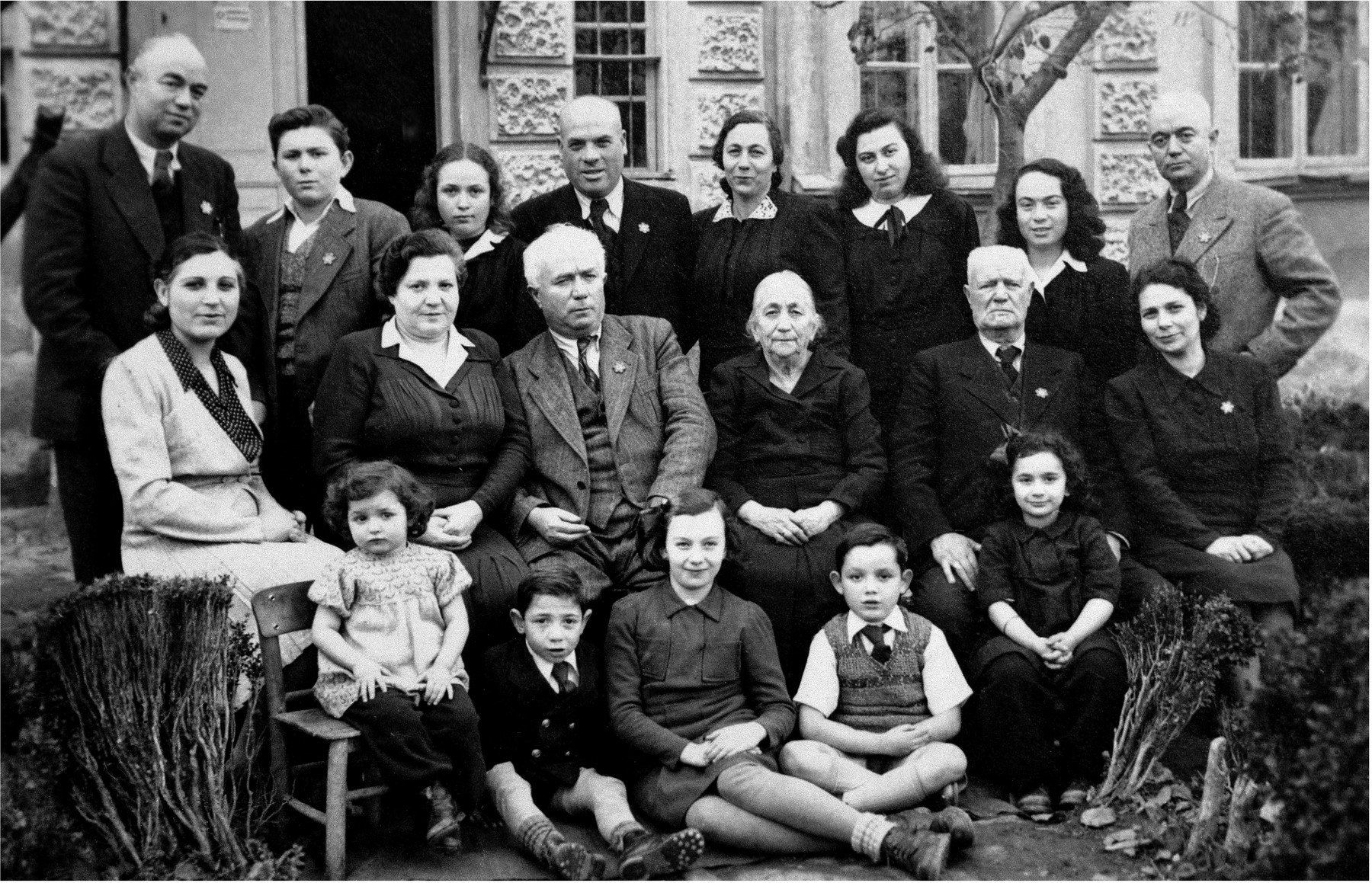 Members of the extended Baruch family pose outside their residence in Kyustendil, Bulgaria, following their expulsion from the capital, Sofia.  During the period of their exile in the provinces, the members of extended Baruch family lived in the home of Miriam and Pinkas Baruch, who had retained their house in Kyustendil after moving to Sofia in the 1930s.  Pictured in the top row, from right to left, are: Samuel Baruch, Ida Haimova, Mimi Baruch, Oretta Haimova, Izhak Haimov, Mary Haimova, Israel Baruch and Joseph Baruch.  In the middle row, from right to left, are: Speranza Baruch, Pinkas Baruch, Miriam Baruch, Yako Baruch, Rachel Baruch and Esther Baruch.  In the front row, from right to left, are: Rosa Baruch, Pinko Baruch, Mary Baruch, Subcho Haimov, Oretta Haimovi and Madlena Baruch.