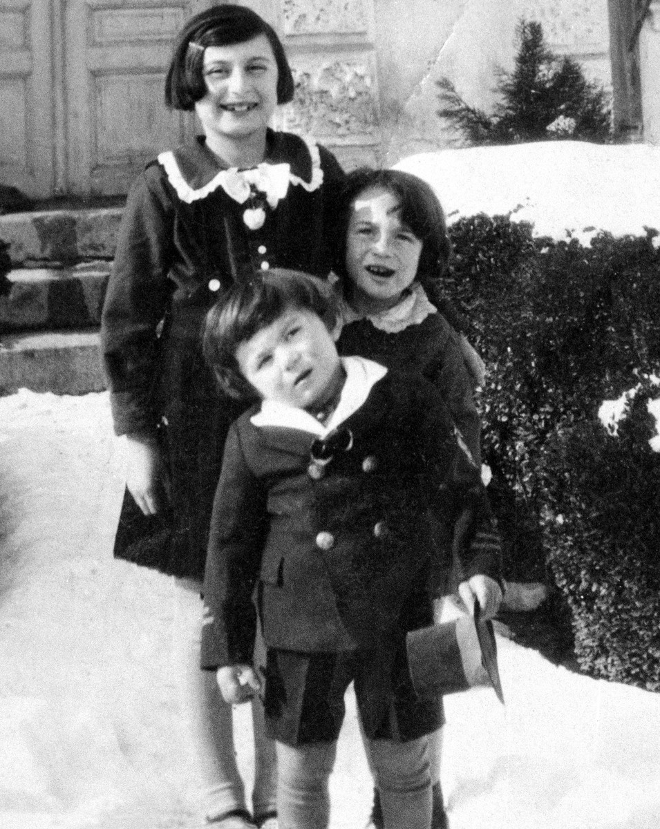 Three Jewish children pose outside in the snow in front of their grandparent's house in Kyustendil, Bulgaria.  Pictured from front to back are: Israel Baruch, Ida Haimova (his first cousin) and Marietta Baruch (his sister).