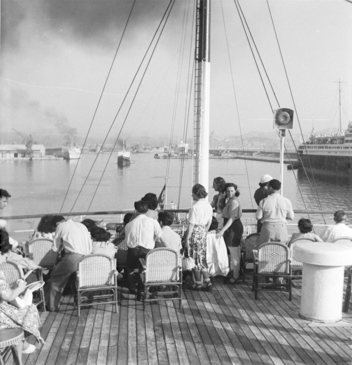 A group of Jewish students sits on the deck of the Kedma as the ship pulls out of the port of Marseilles on its way to Haifa, where they will be attending a meeting of the World Jewish Students.