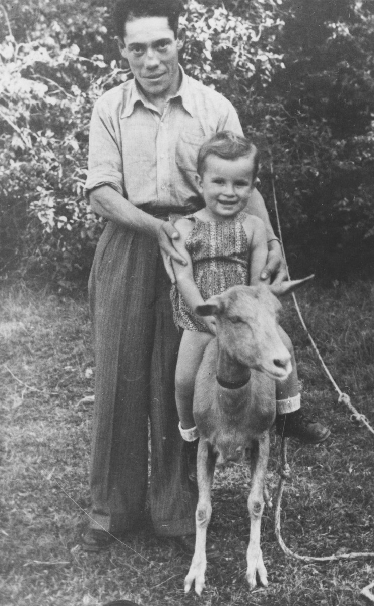 A Jewish DP living in the Heidenheim displaced persons camp, holds his son, who is riding on a goat.  The child pictured is David Elbaum.