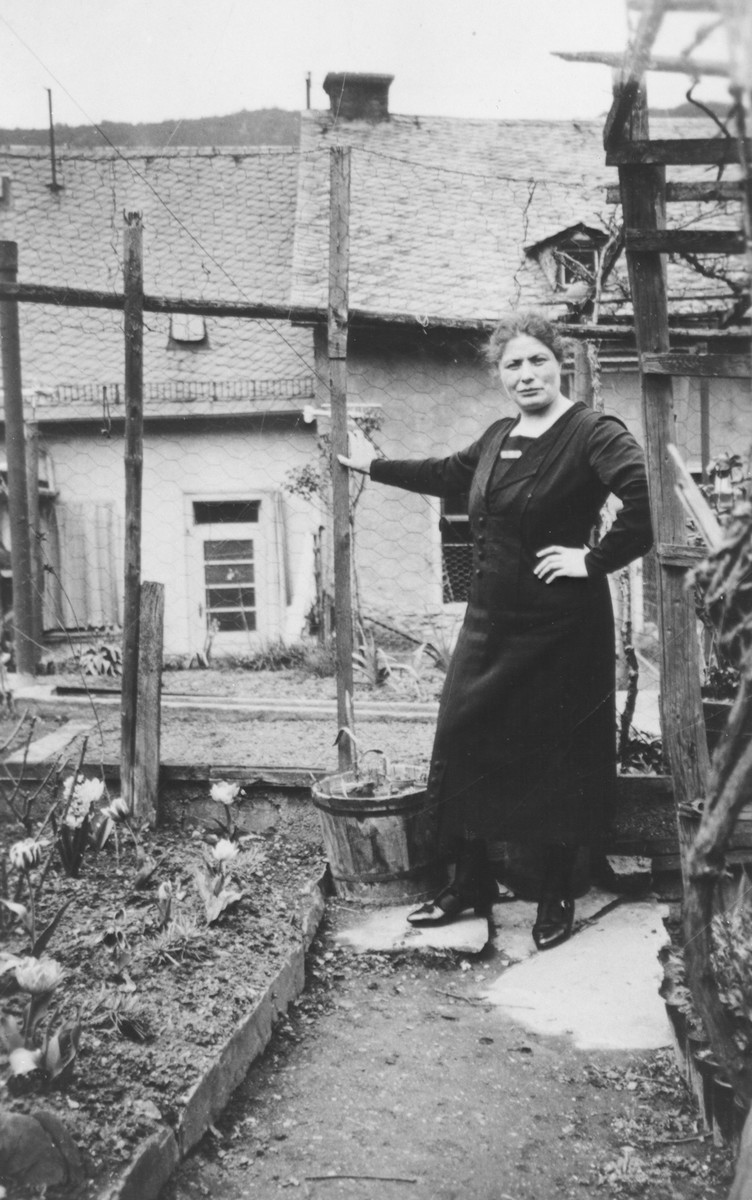 Else Trum (sister of Erna Gottschalk) poses for a photograph in a small garden.