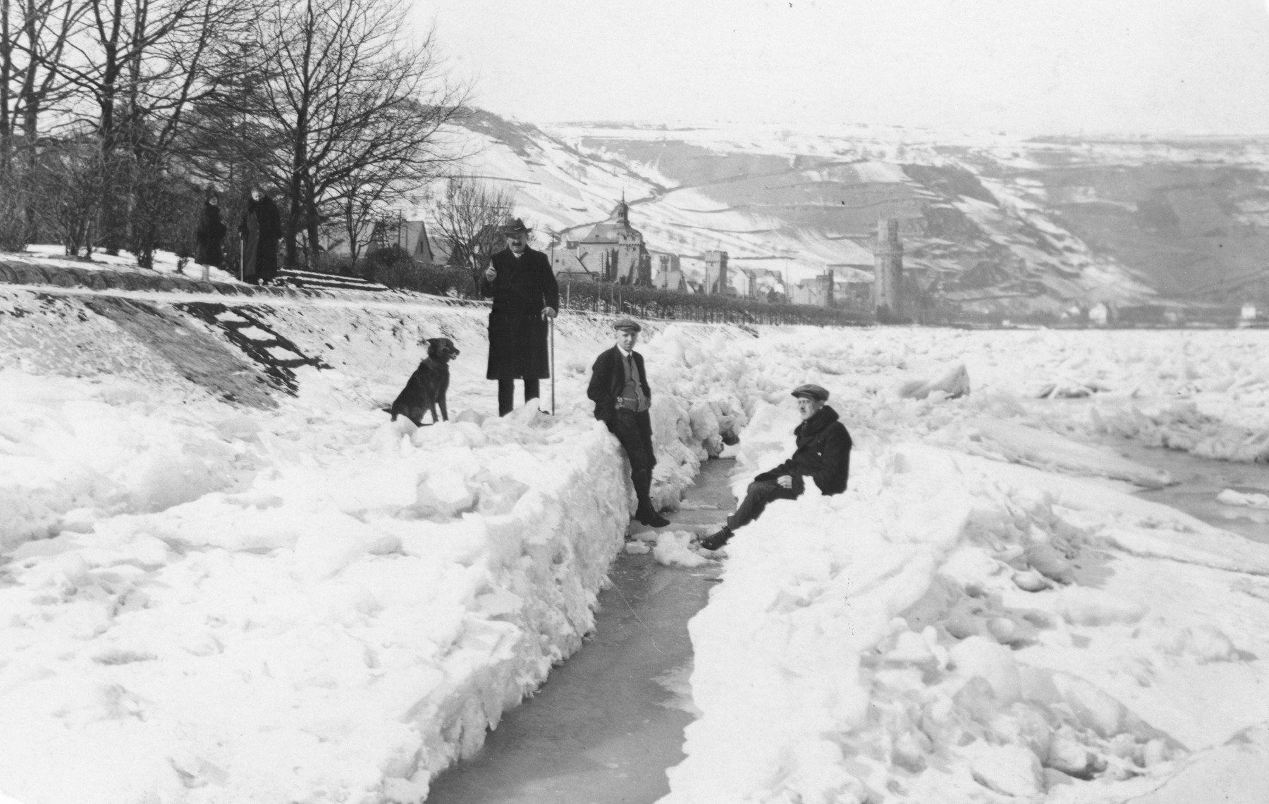 Gustav Gerson (left) with his dog and other two men on the frozen river Rhein, in the background is the town of Oberwesel.