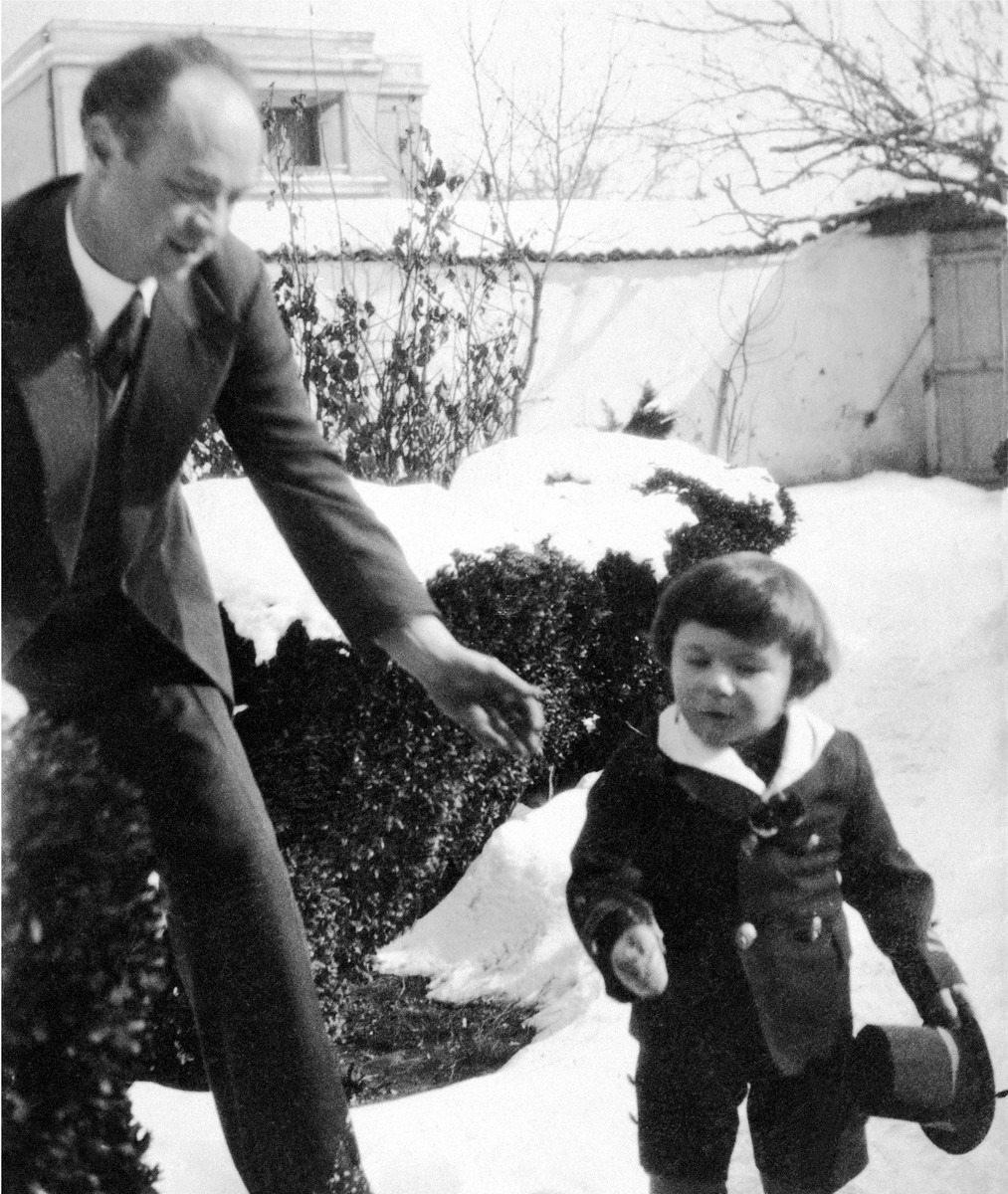 A Jewish child stands outside in the snow in front of his grandparent's house in Kyustendil, Bulgaria.  His uncle reaches out to him.  Pictured are Israel Baruch with his uncle Joseph Baruch.