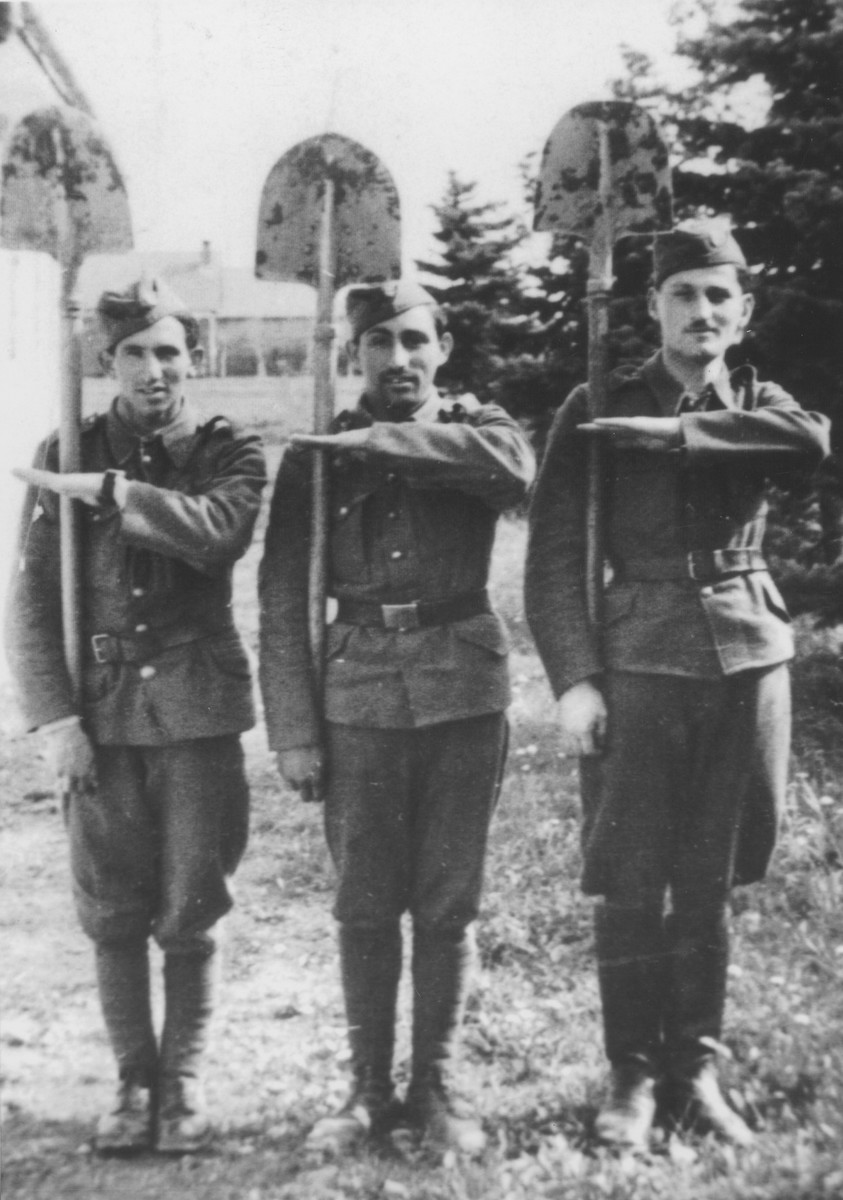 Three members of the 6th Labor Battalion stand at attention with their shovels.